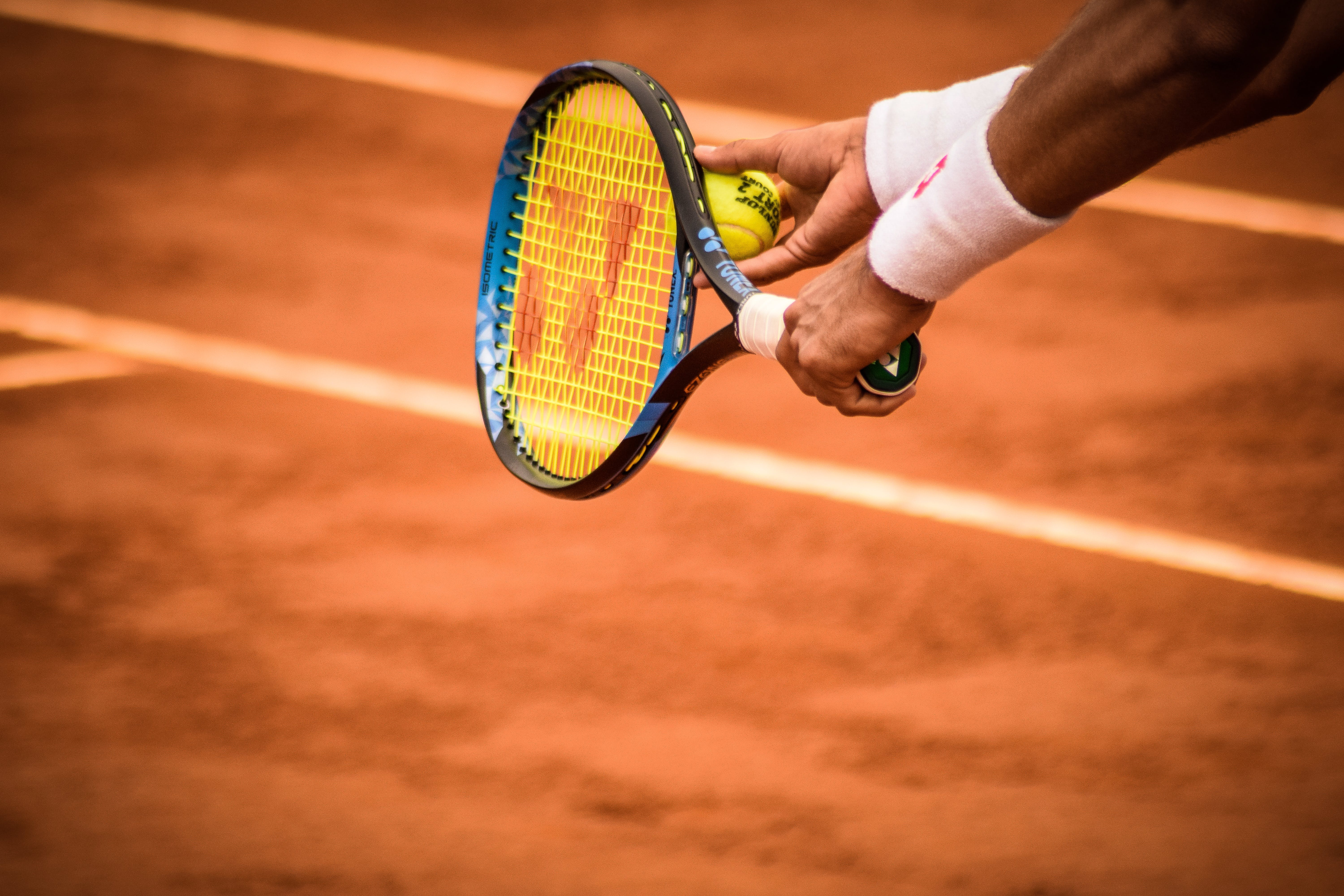 Close-Up Photo of Person Holding Tennis Racket and Ball