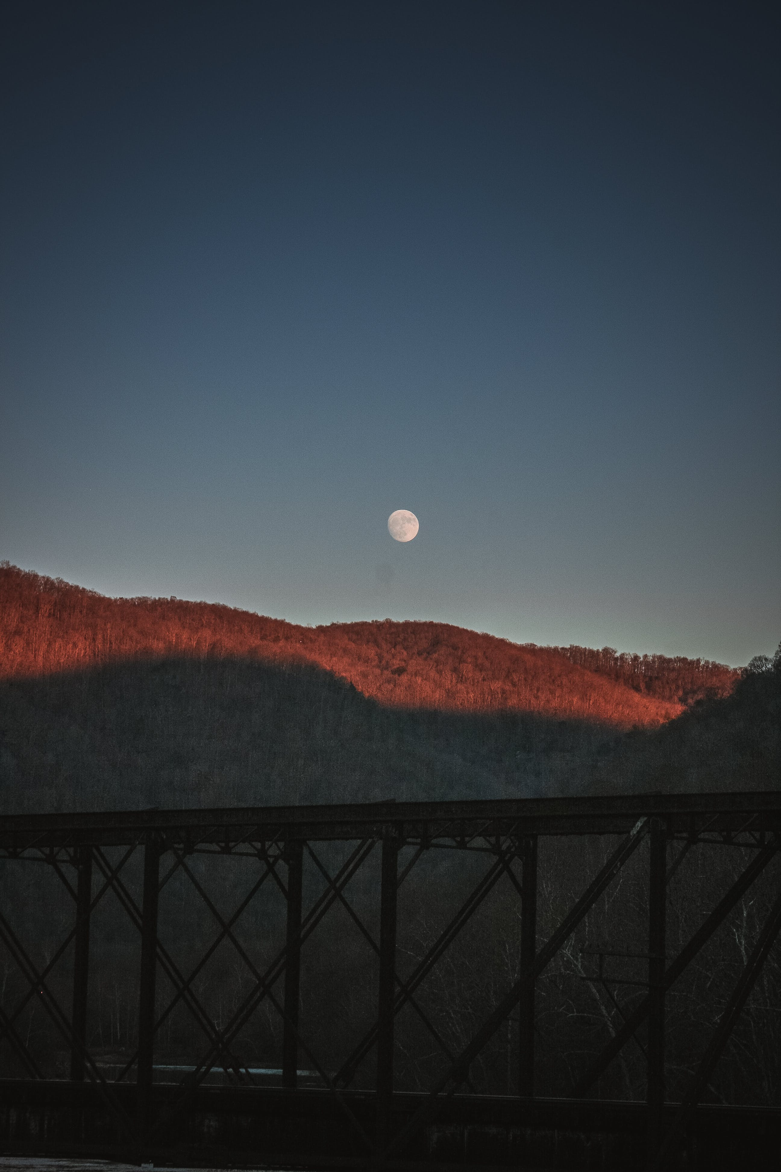 Silhouette Photography of Bridge Under Moon by Day
