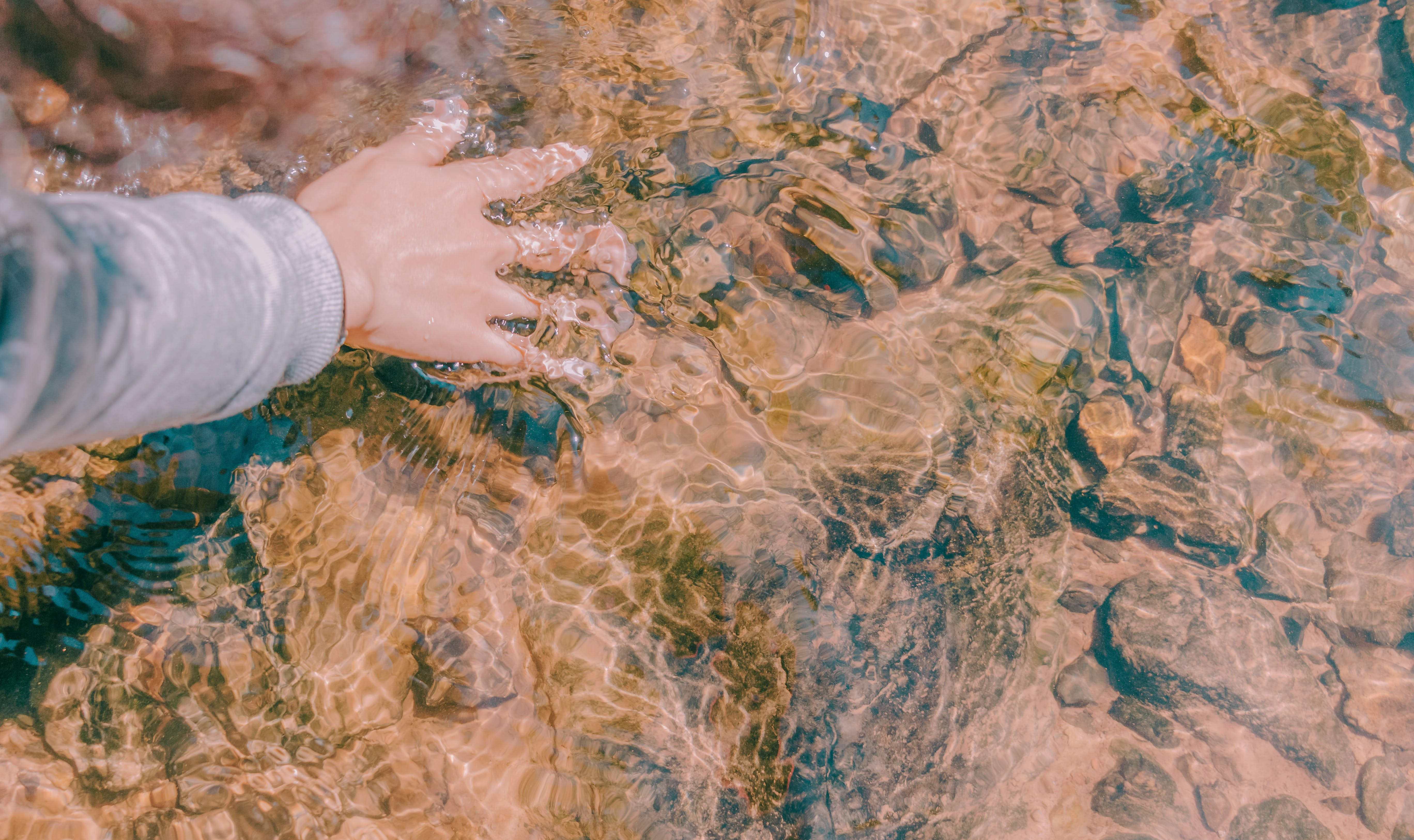 Person's Right Hand Touching Body of Water