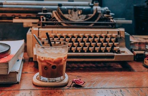 Café Frío En Vidrio Cerca De La Máquina De Escribir