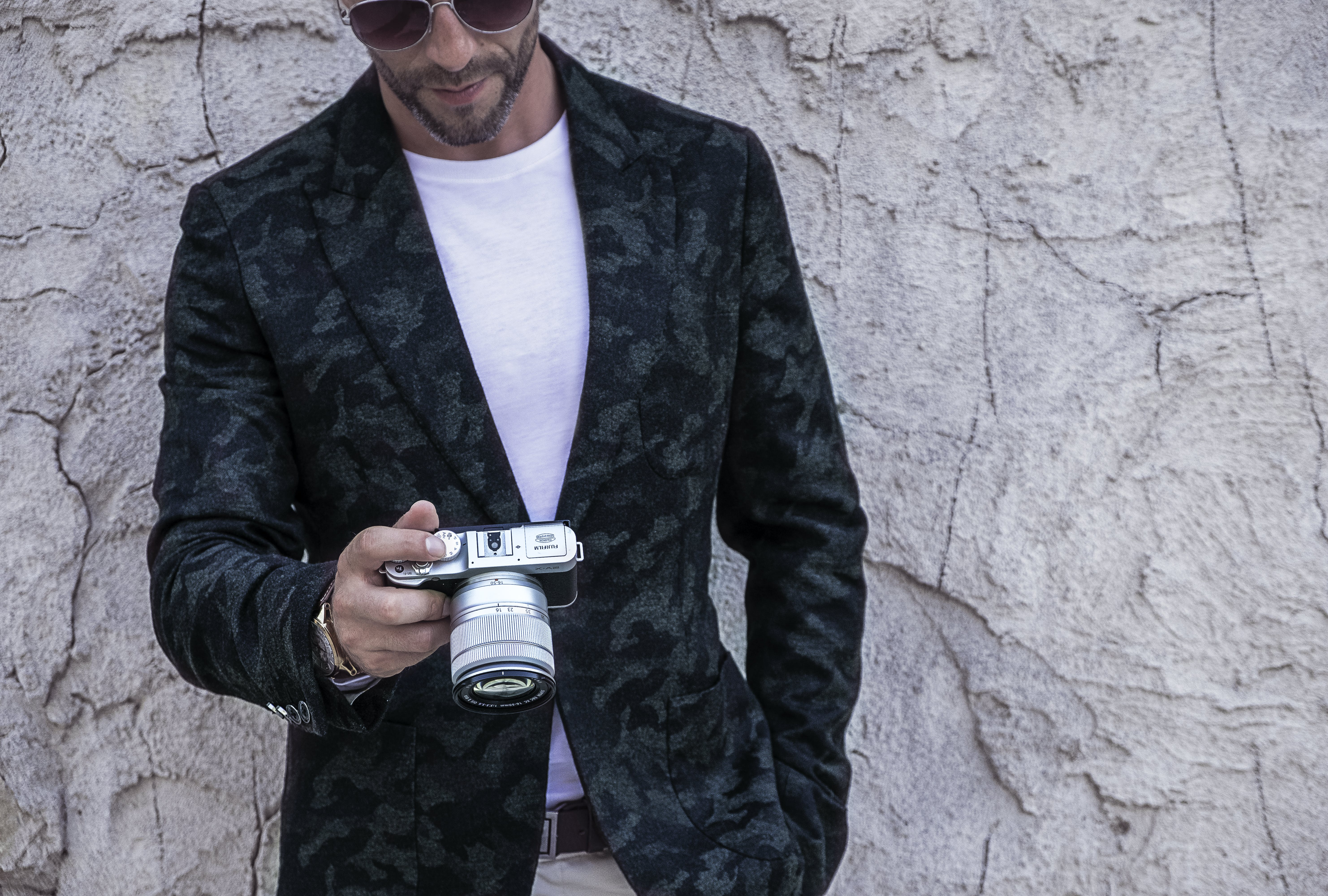 Man in Blue and Black Camouflage Coat Holding Silver Dslr Camera Standing in Front of Gray Concrete Wall