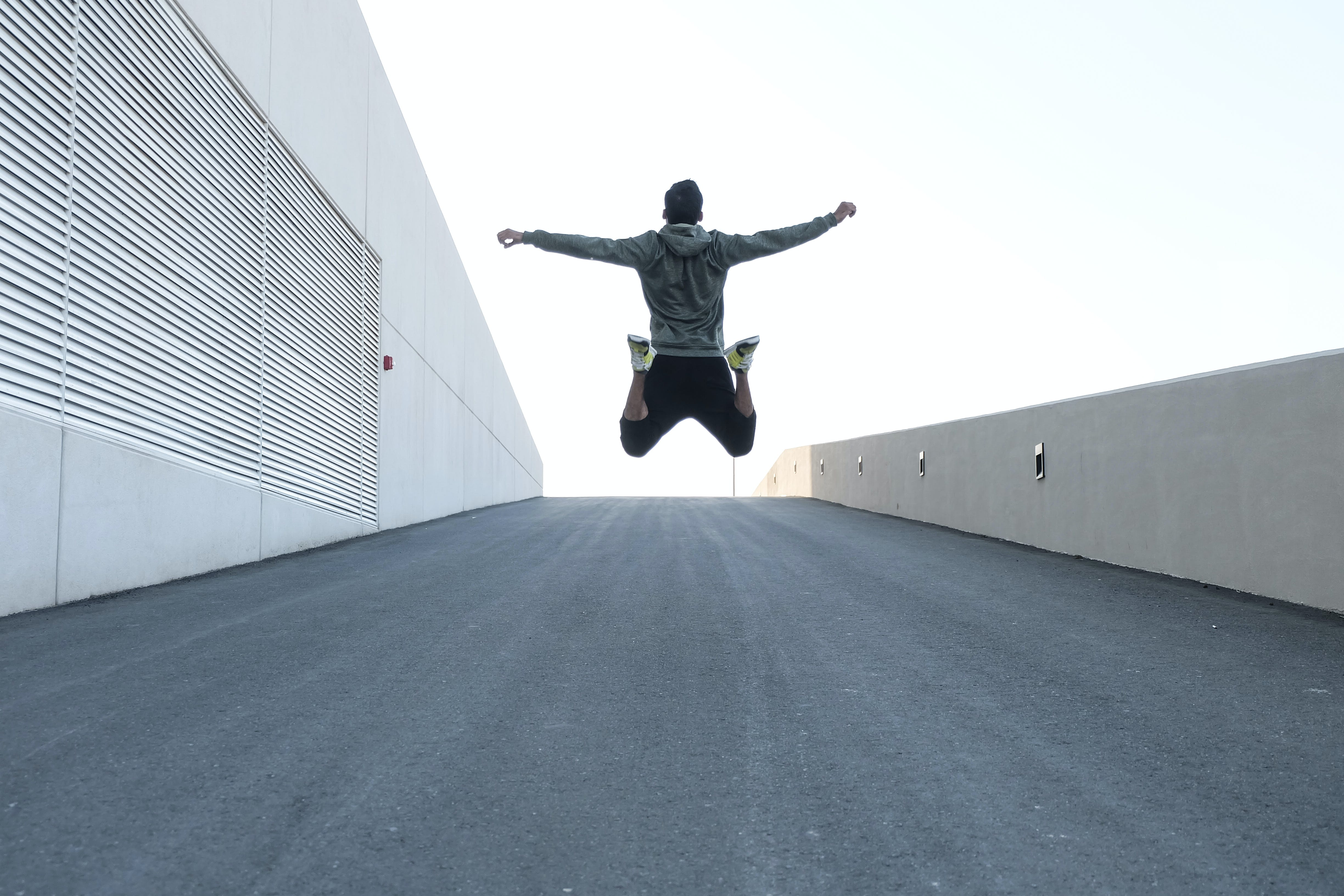 Man in Gray Hoodie Jump With Open Arms
