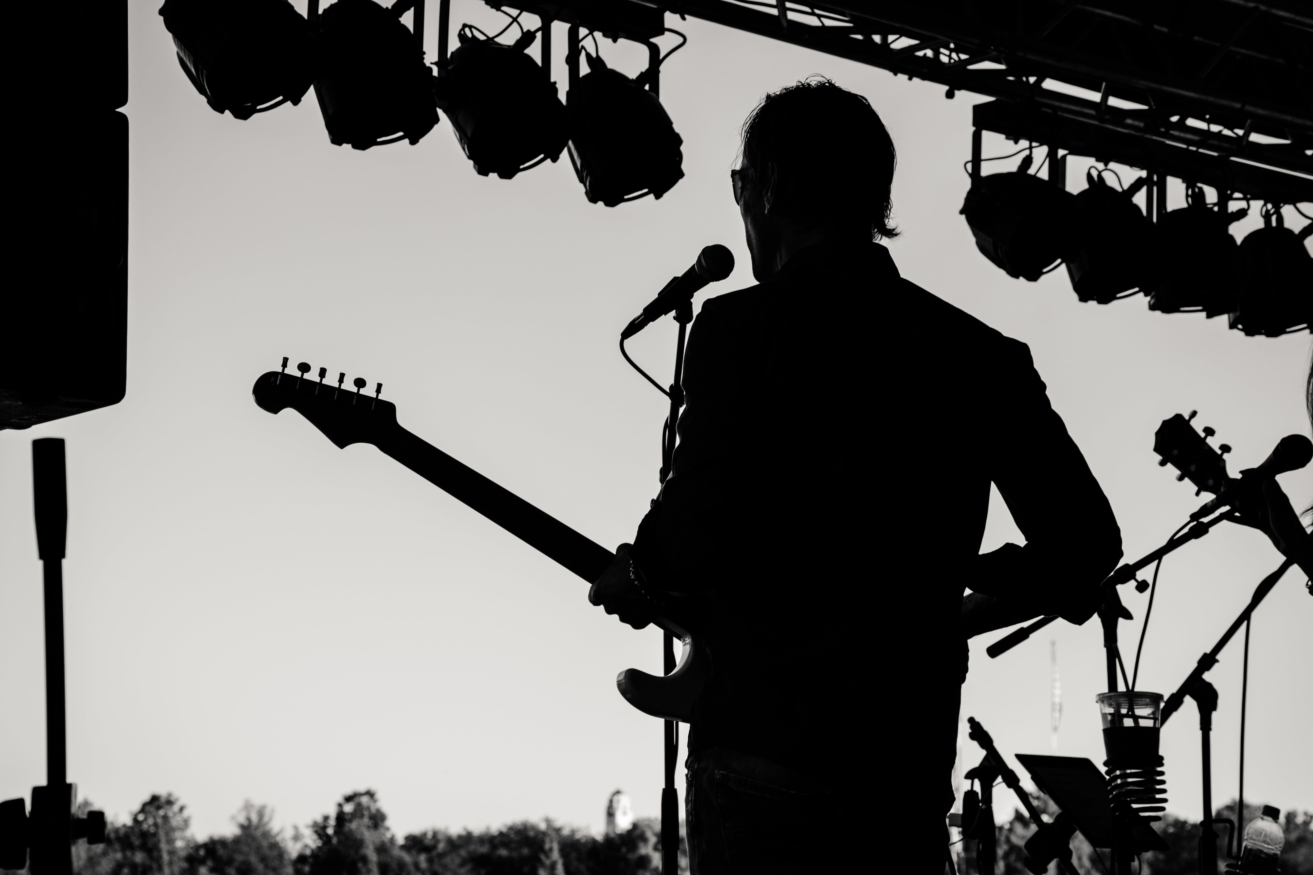Silhouette Photo of Man Holding Guitar