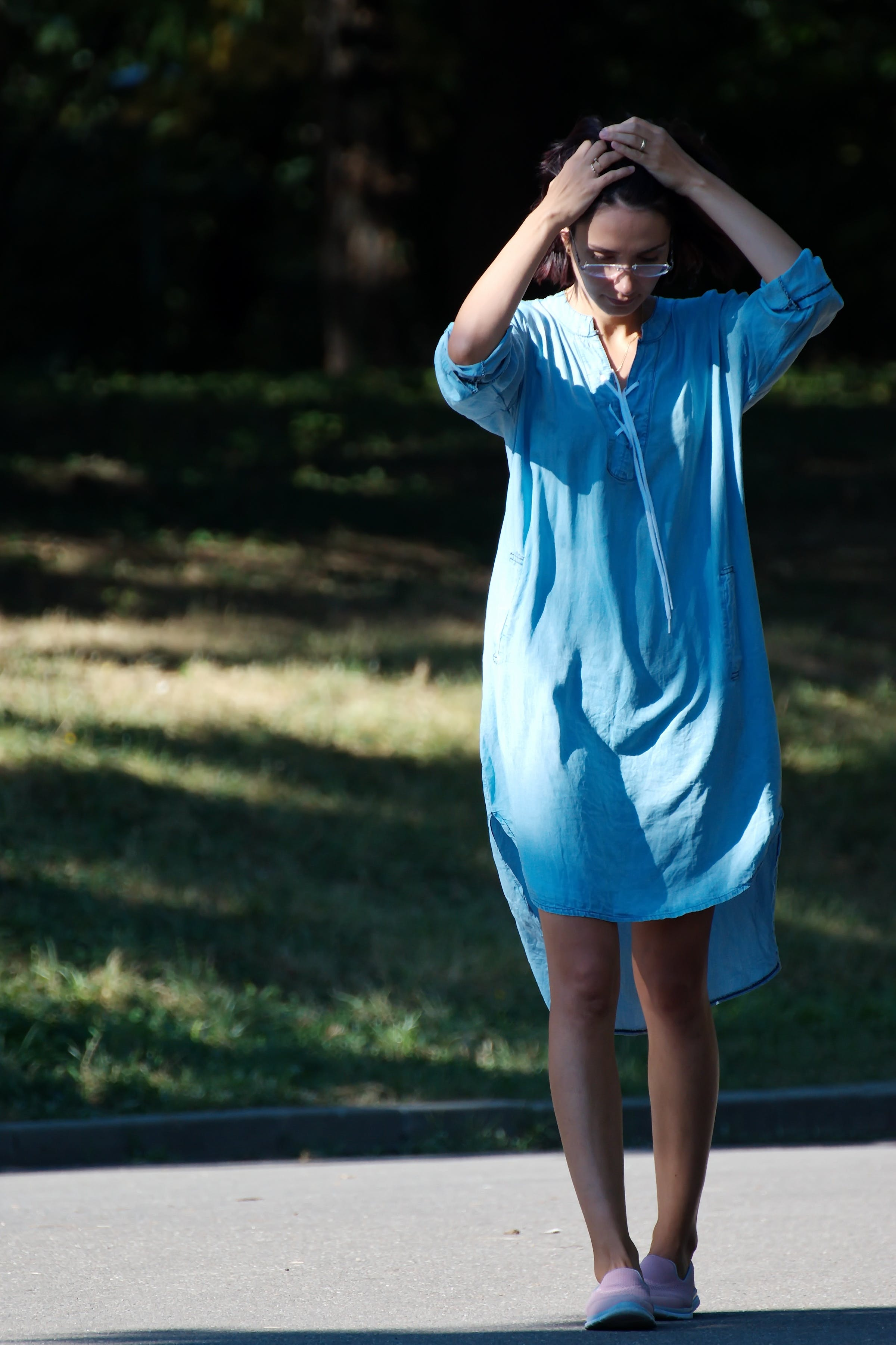 Woman in Blue Tunic Holding Her Hair