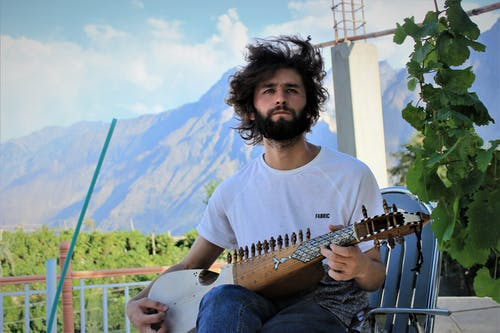 Kostenloses Stock Foto zu geblasene haare, holding-instrument, junge, musik spielen