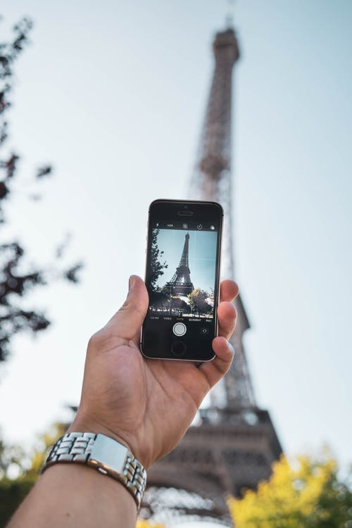 Person Taking Photo of Eiffel Tower