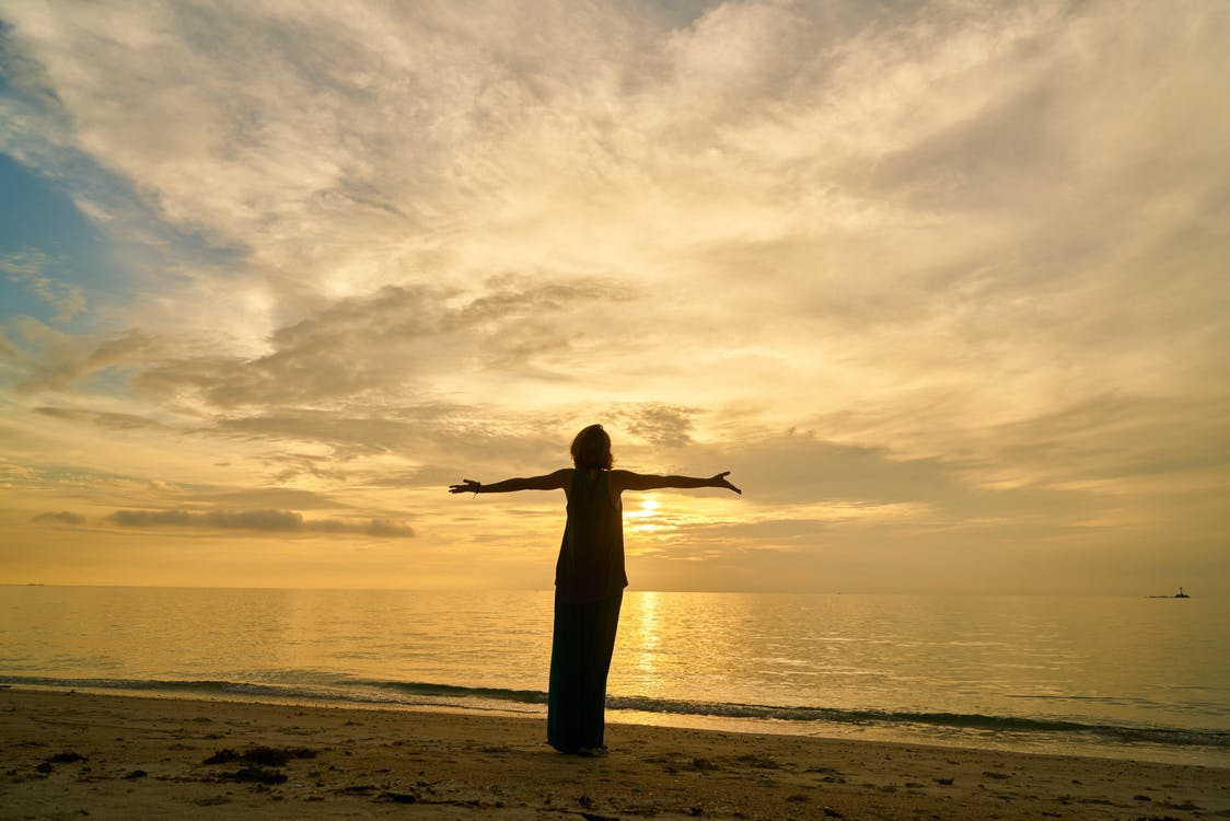 Silhouette of a Woman Stretching Her Arms Facing the Ocean
