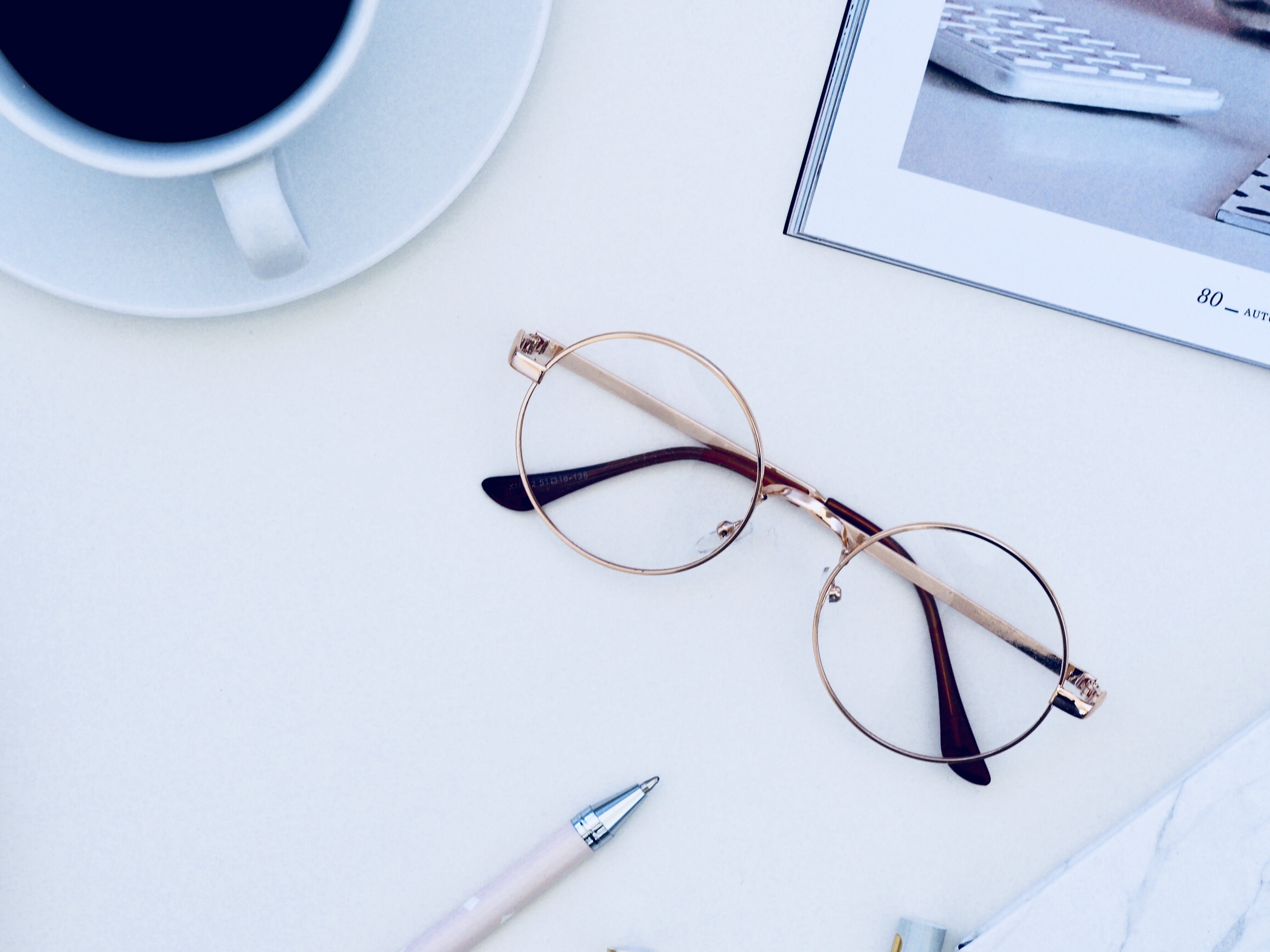 Brown Framed Eyeglasses Near Cup of Coffee on White Surface