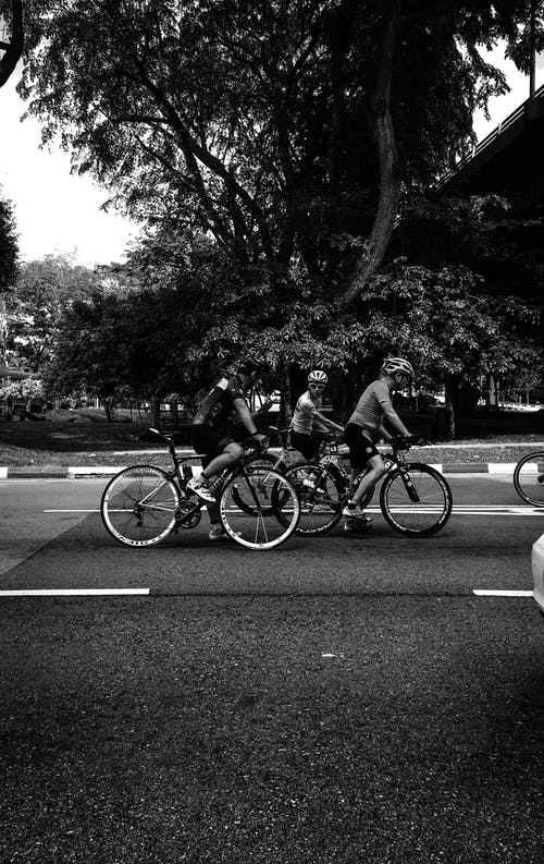 Monochrome Photography of People On Bicycle