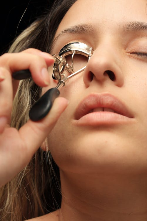 Woman Using Eyelash Curler Close-up Photography