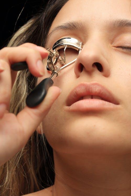 Woman Using Eyelash Curler Close-up Photography