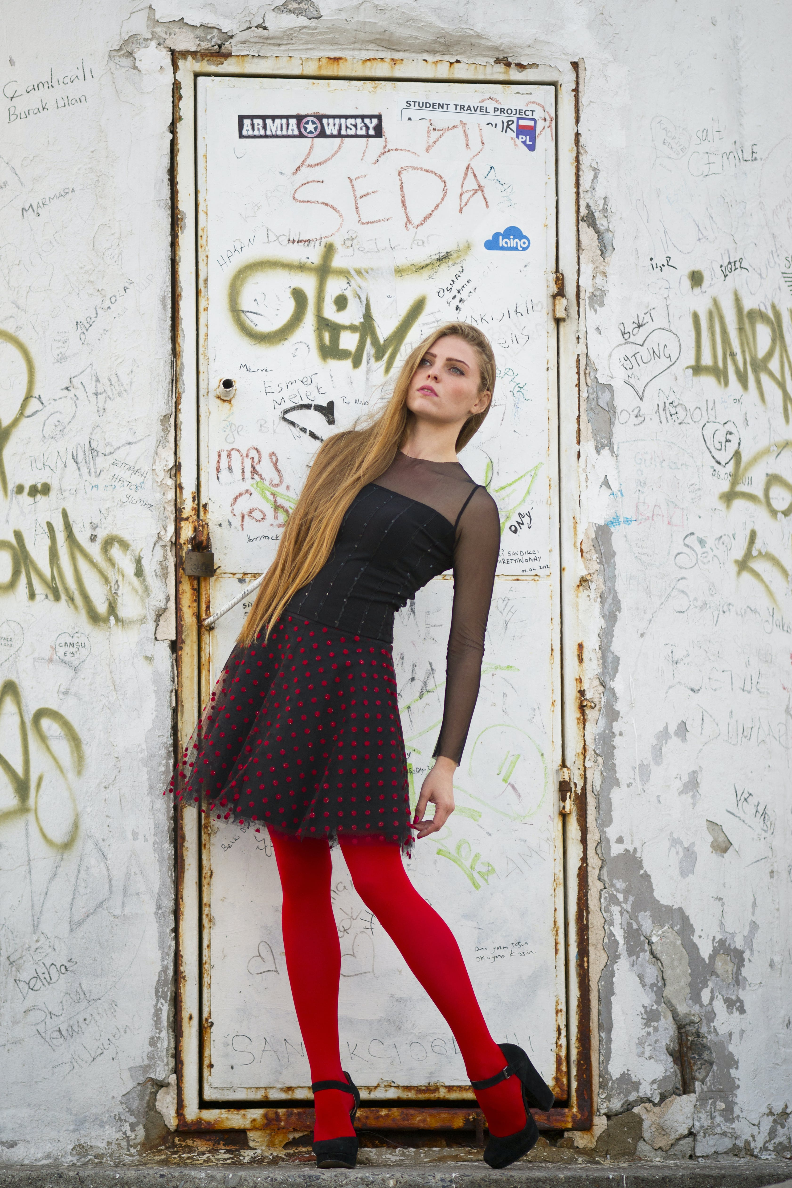 Woman Wearing Black and Red Long-sleeved Mini Dress and Red Leggings in Front of a Closed White Metal Door