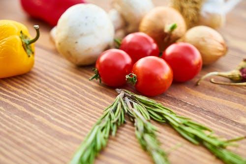 ローズマリーと他のスパイスの近くの赤いトマトのクローズアップ写真