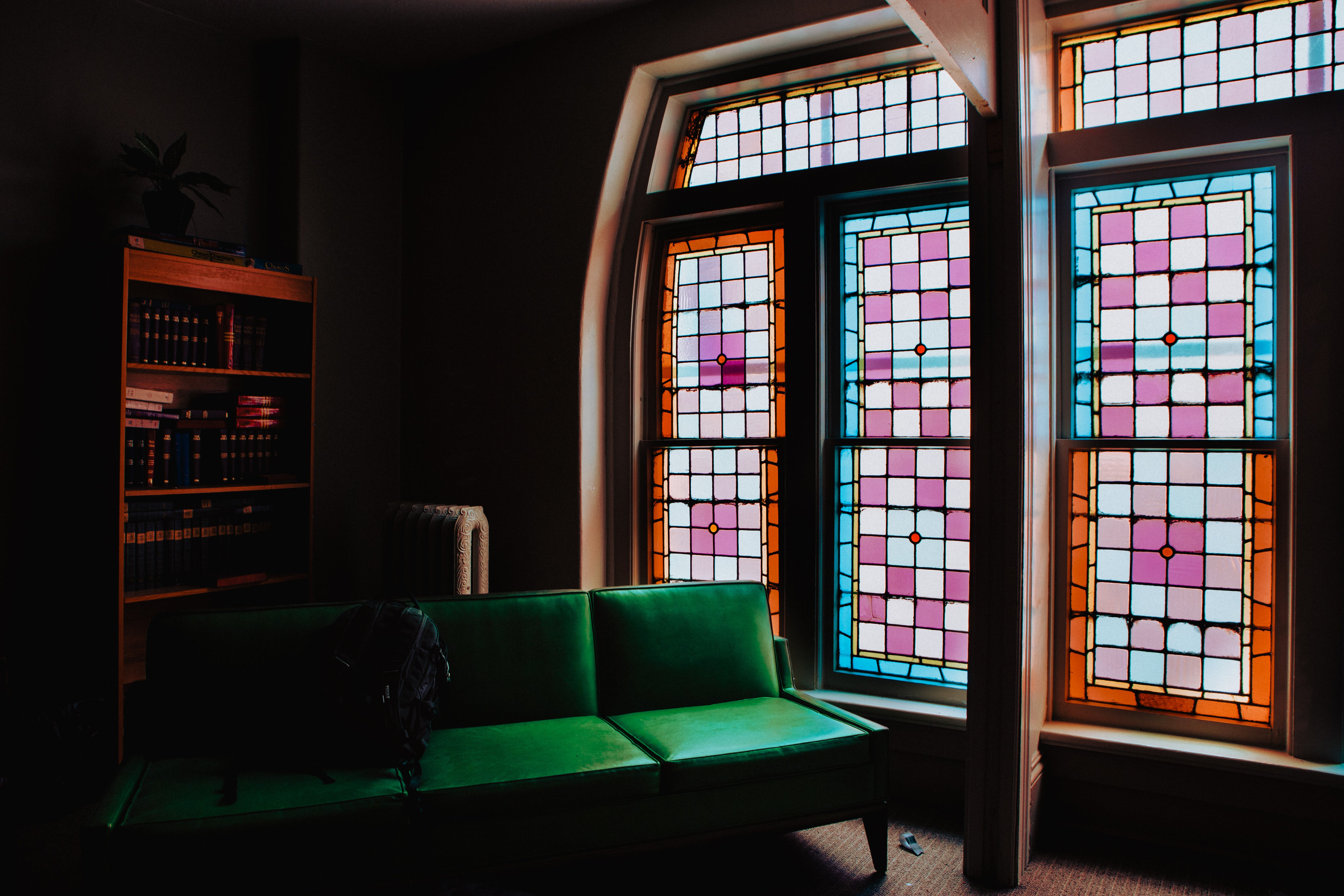 Green Leather Couch Beside of Stained Glass Window