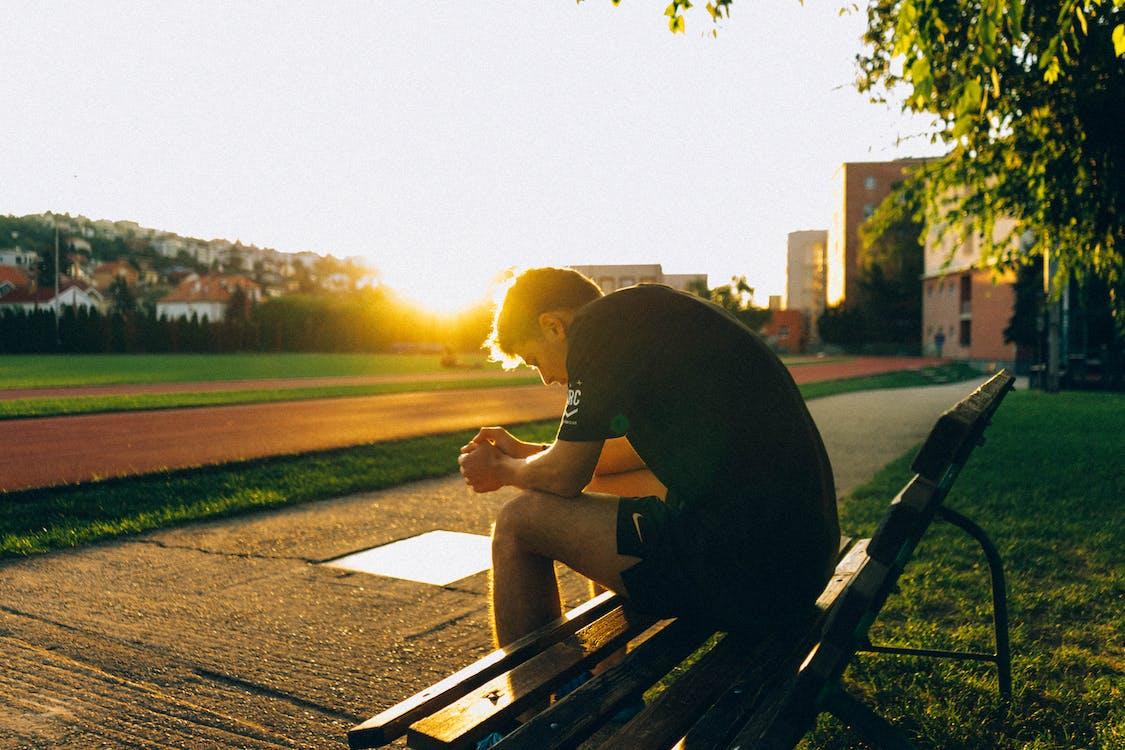 Hombre Sentado En Un Banco Cerca De La Pista De Campo Mientras Se Pone El Sol