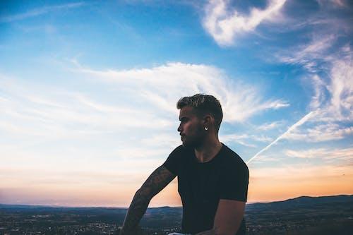 Man Sitting Under the Blue Skies