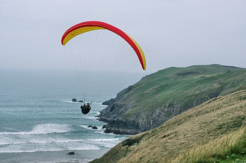 Free stock photo of cliff, fun, paraglider, sea
