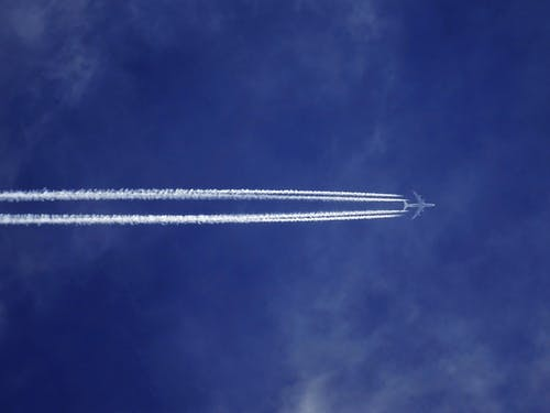 Bottom View of Plane With Contrail
