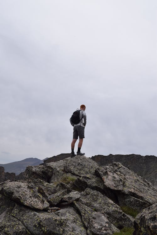 Man With Black Backpack Standing on Rock