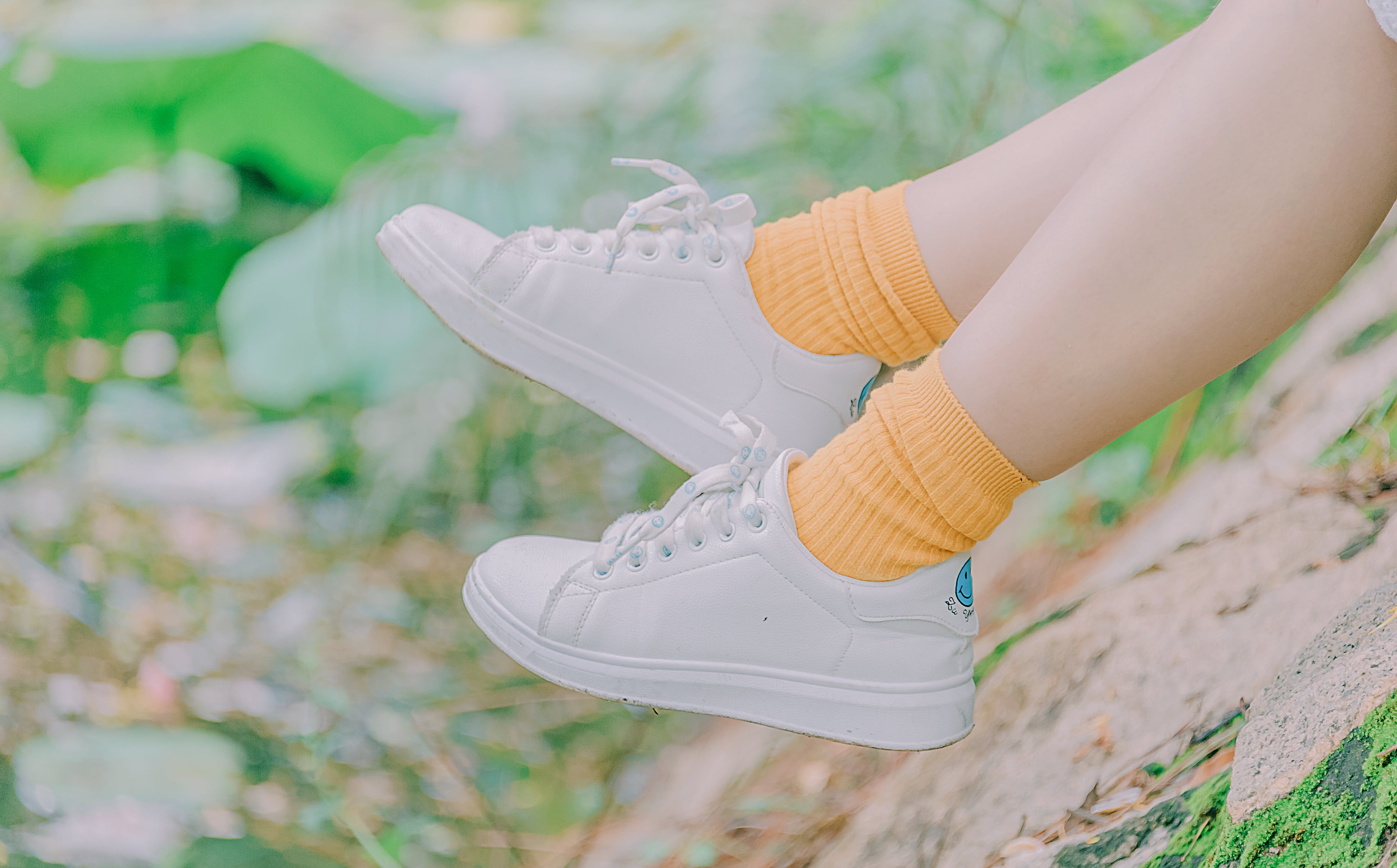 Person Wearing Pair of White Low-top Sneakers and Orange Crew Socks