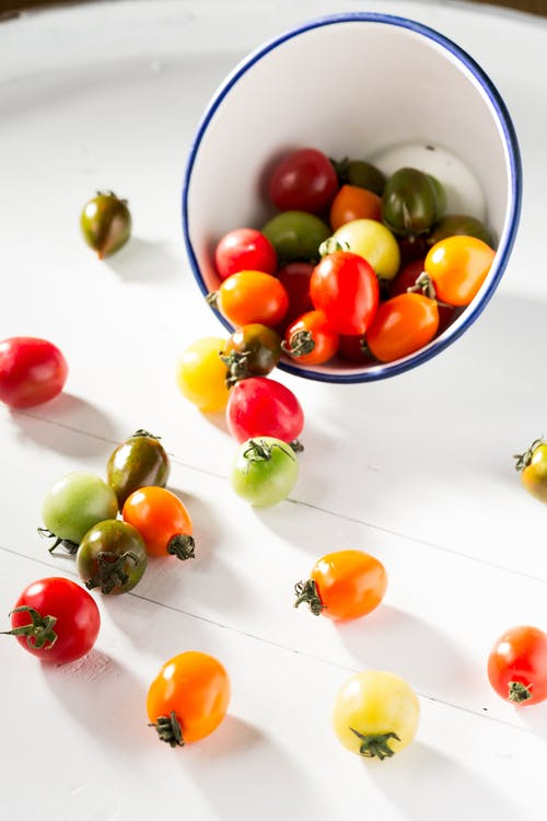 Assorted-color Tomatoes in White Bowl and on White Surface