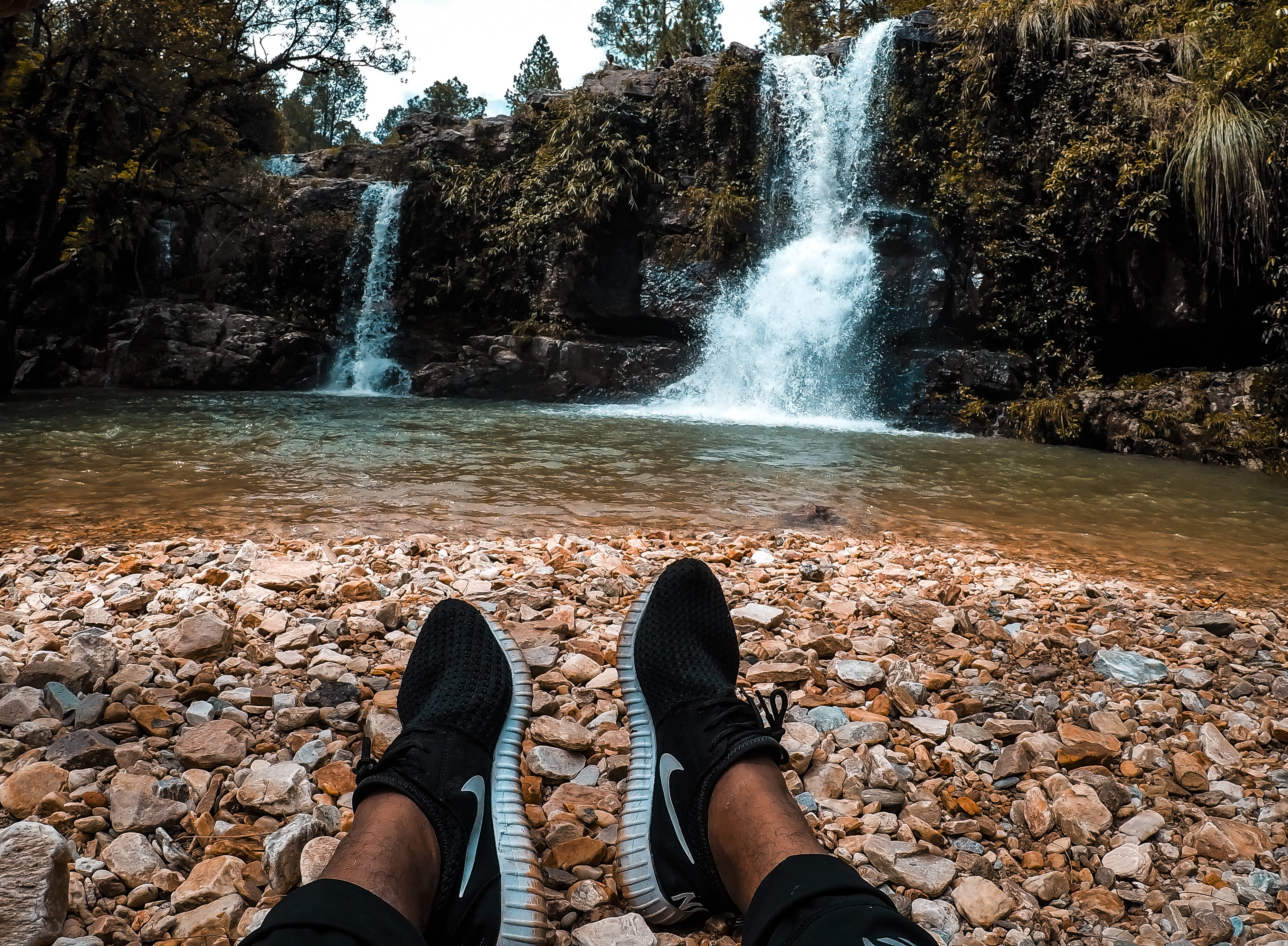 Person Resting on Ground Facing Waterfalls