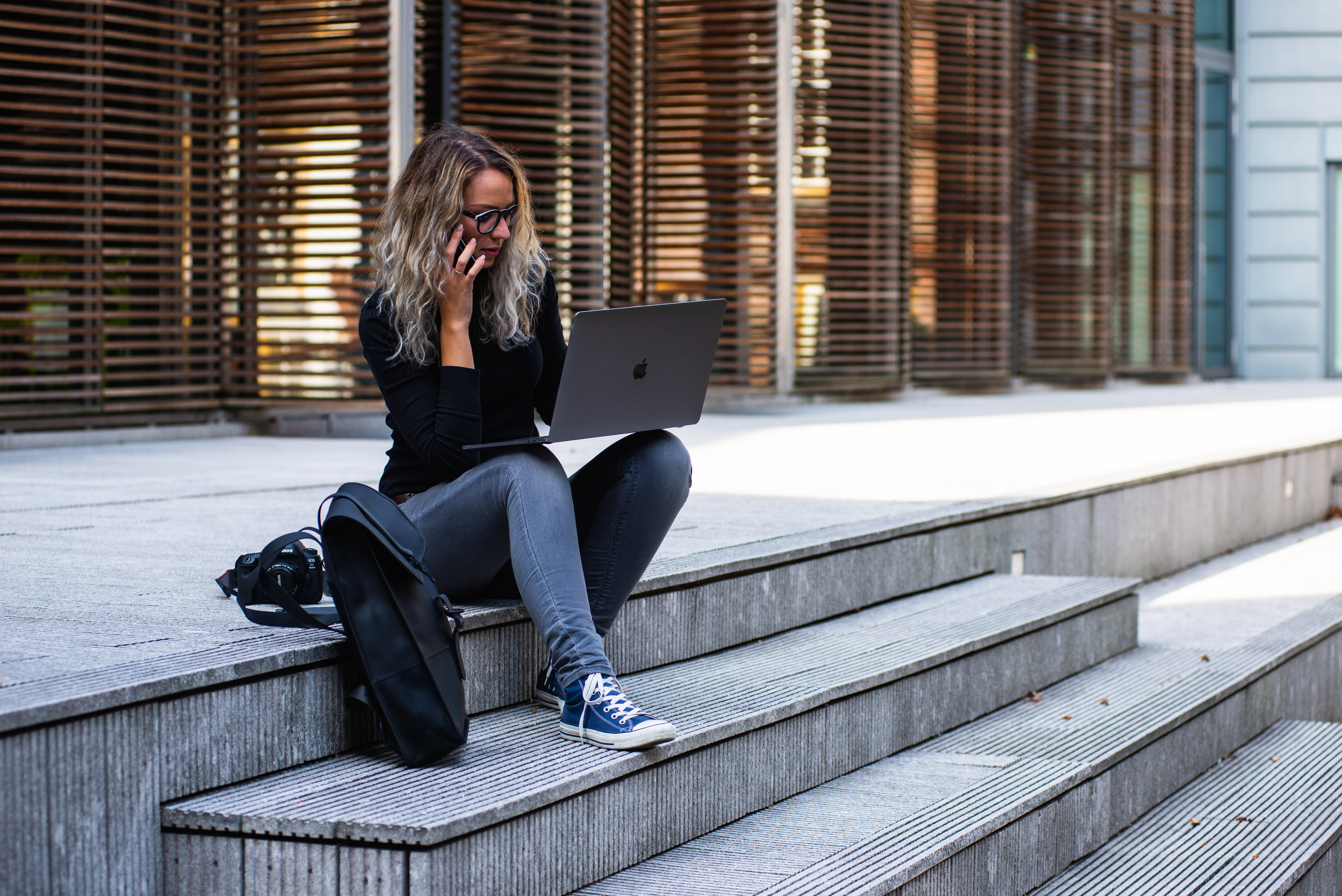 Woman Sitting on Stairs While Using Laptop