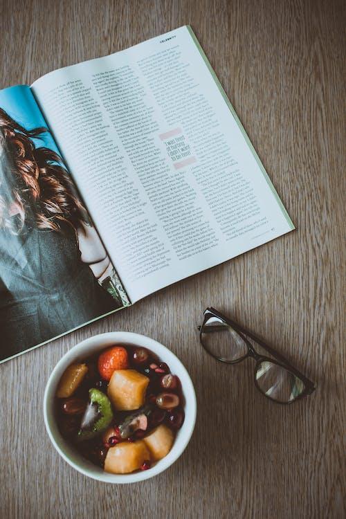 Очки рядом с миской с едой и журналом на столе