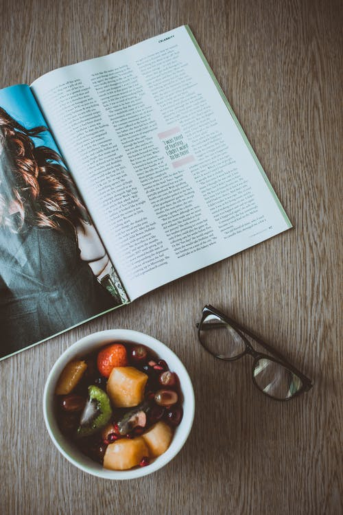 Eyeglasses Beside Bowl of Food and Magazine on Table