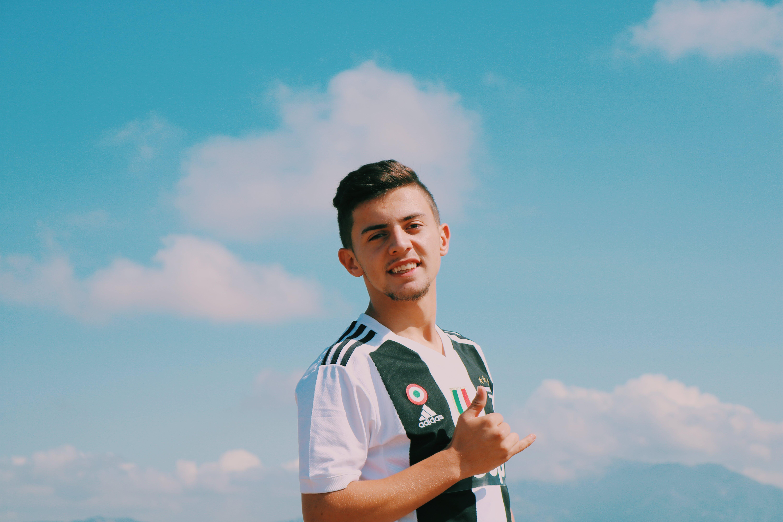 Man Wearing White and Green Adidas V-neck Jersey Shirt Smiling