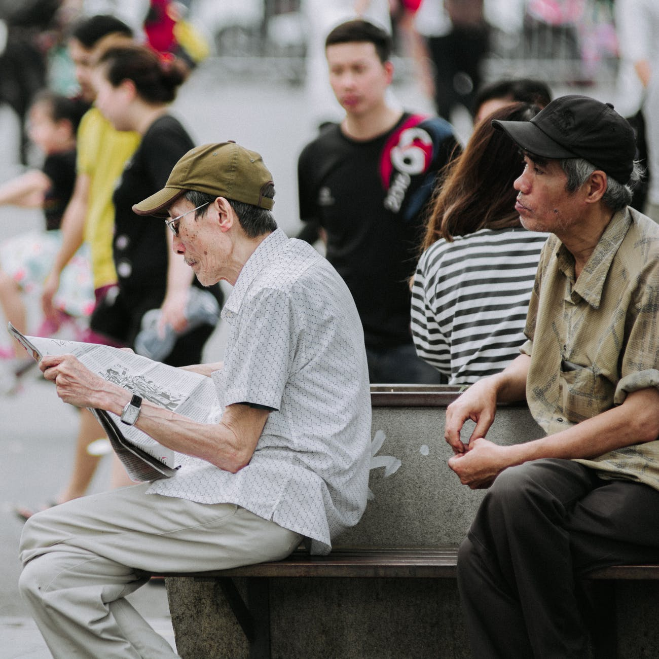 old man reading the newspaper in a crowded area