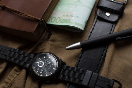 100 Euro Banknote Beside Round Black Chronograph Watch