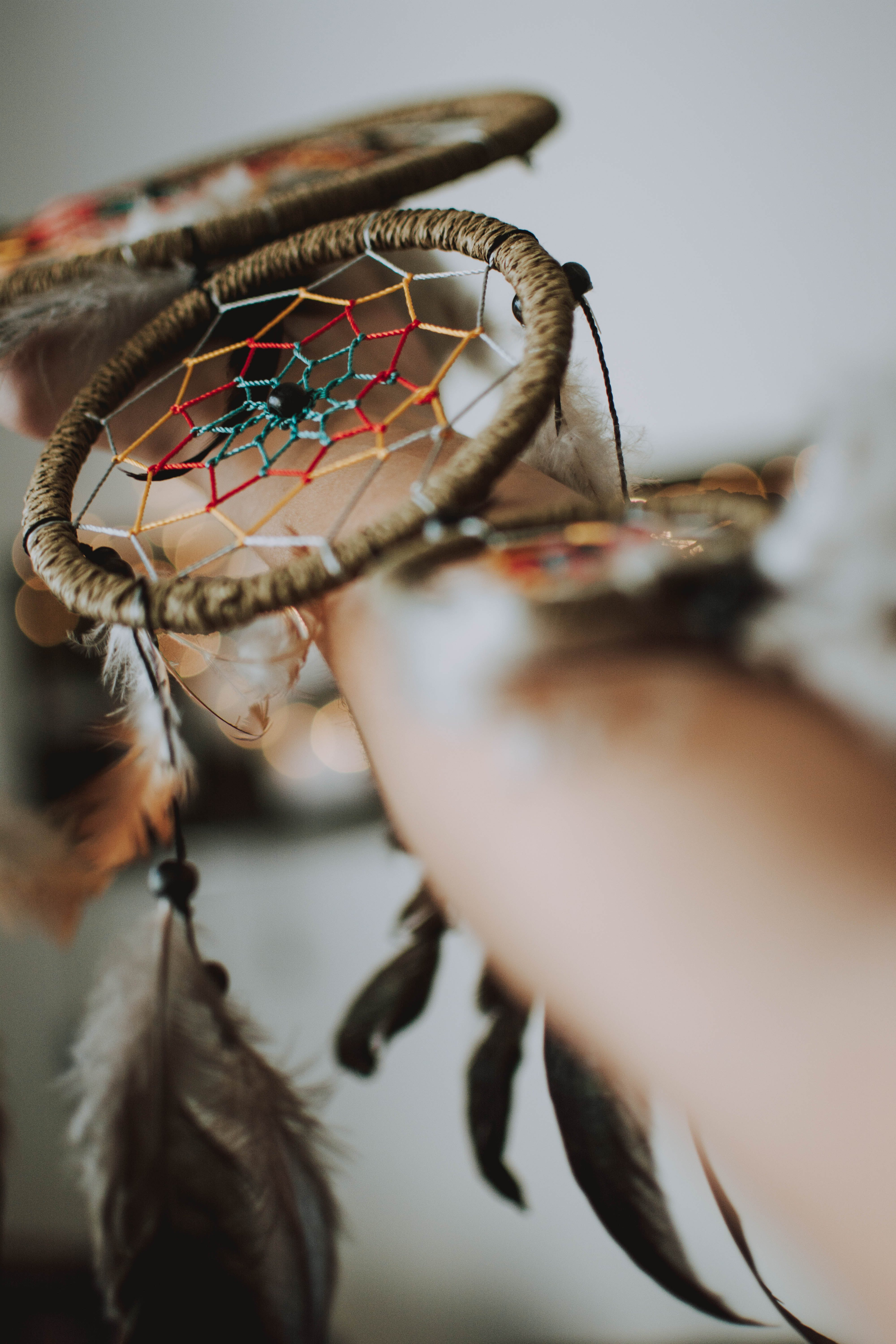 Person Holding Brown and Red Dreamcatcher