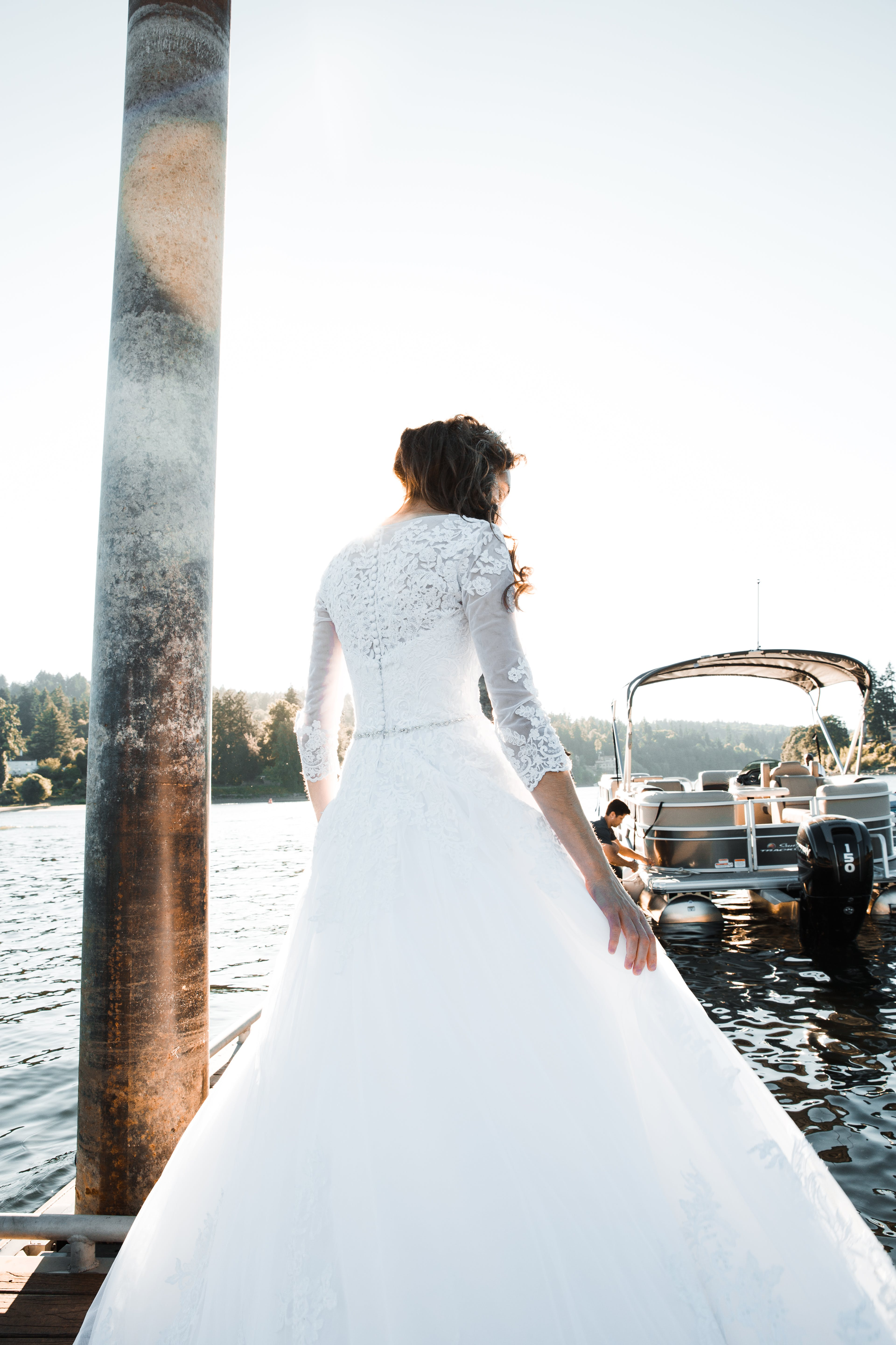 Woman in White Wedding Gown Standing Near Body of Water
