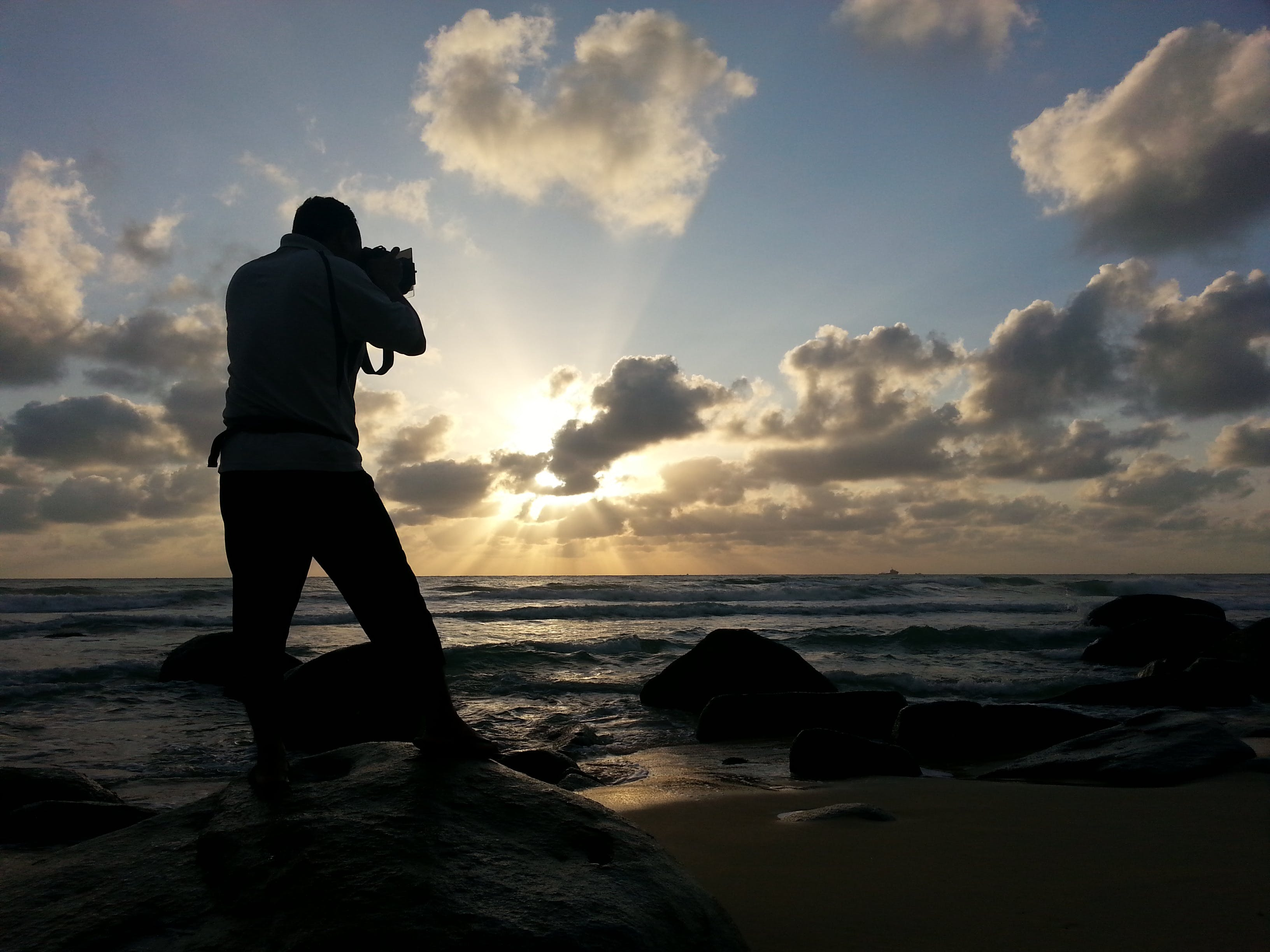 Person Capturing Photo Near Sea Under Clear Blue and White Cloudy Sky during Daytime