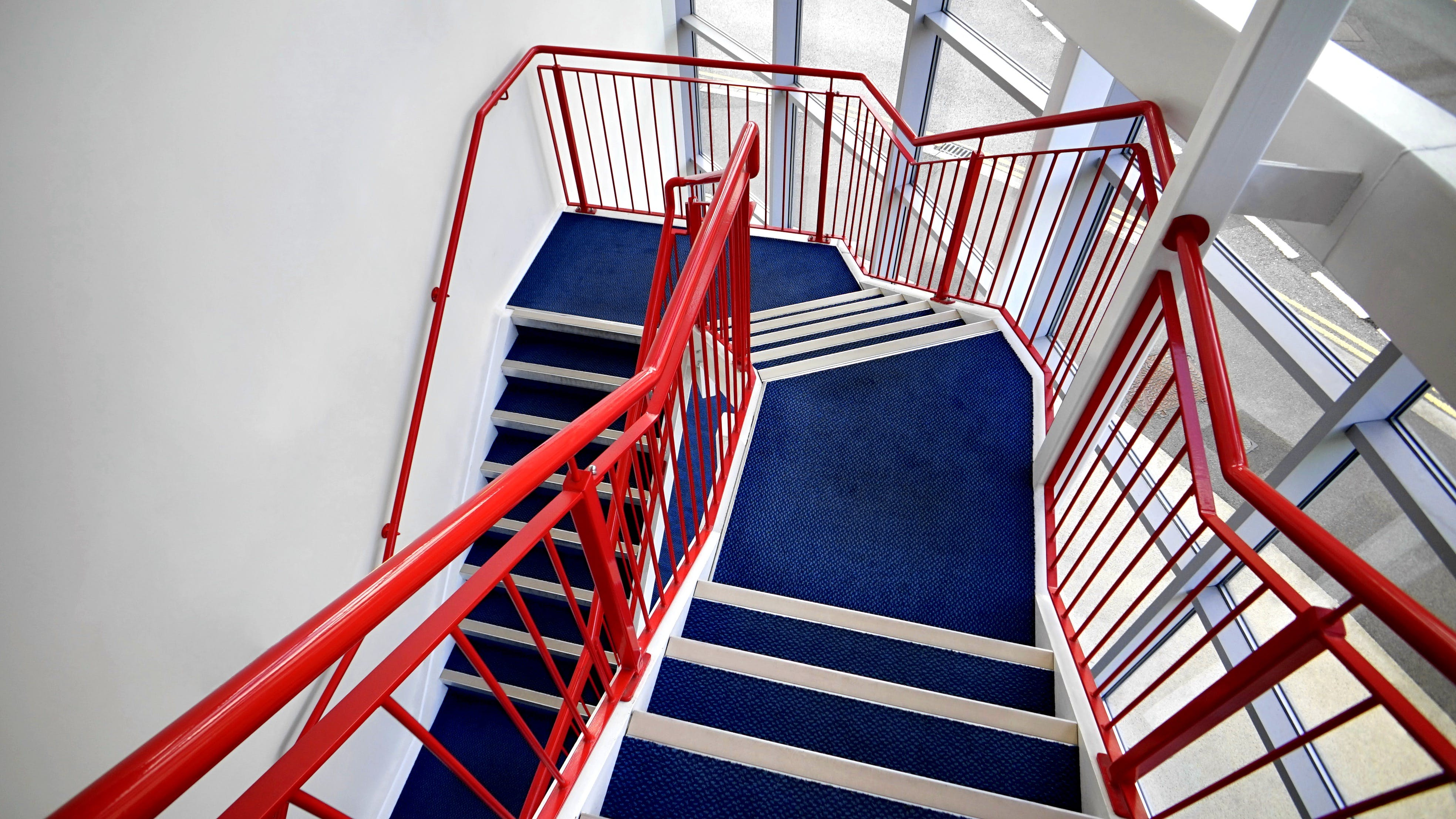 Blue Stairs and Red Handled on White Paint Wall