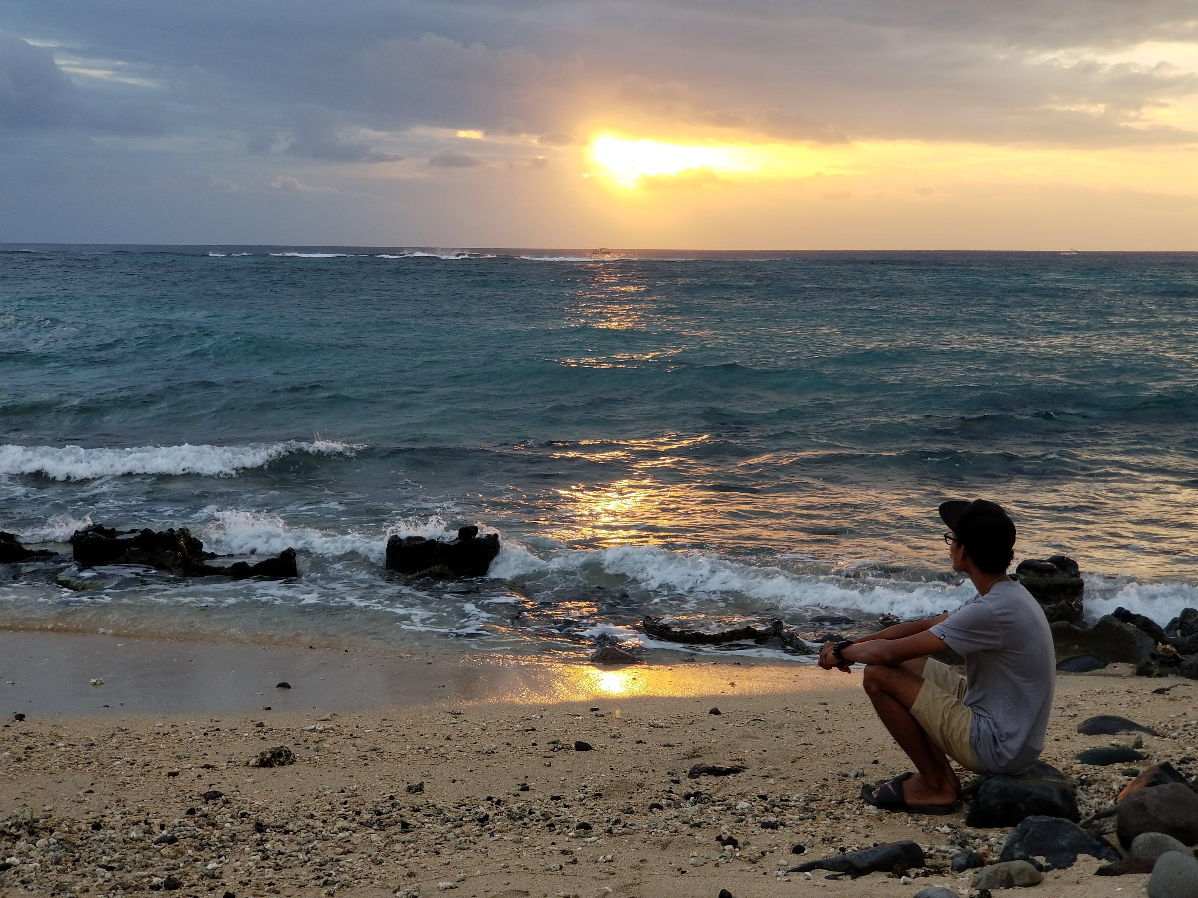 Man Sitting by the Beach Looking at Setting Sun