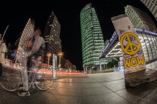 Man Riding Bicycle on Sidewalk Near Buildings during Nighttime