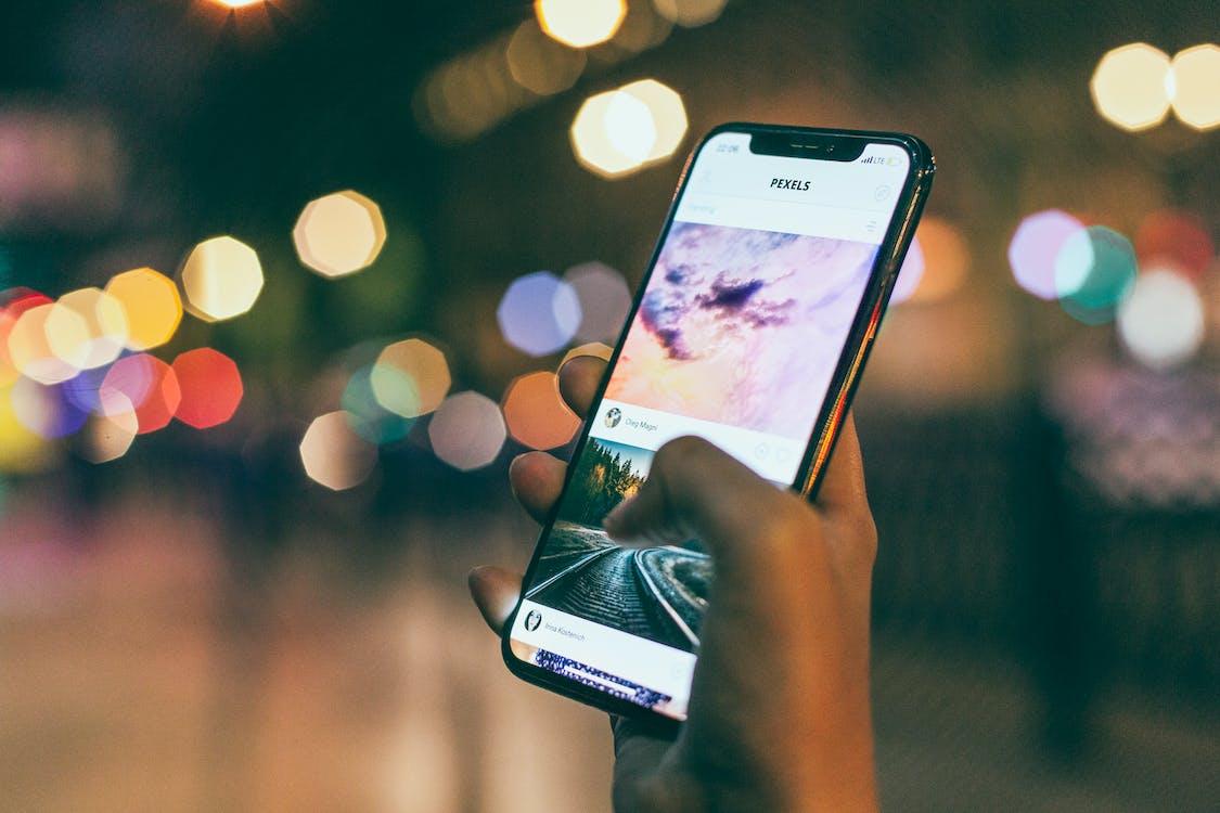 Fotografía Bokeh De Una Persona Con Un I Phone Encendido