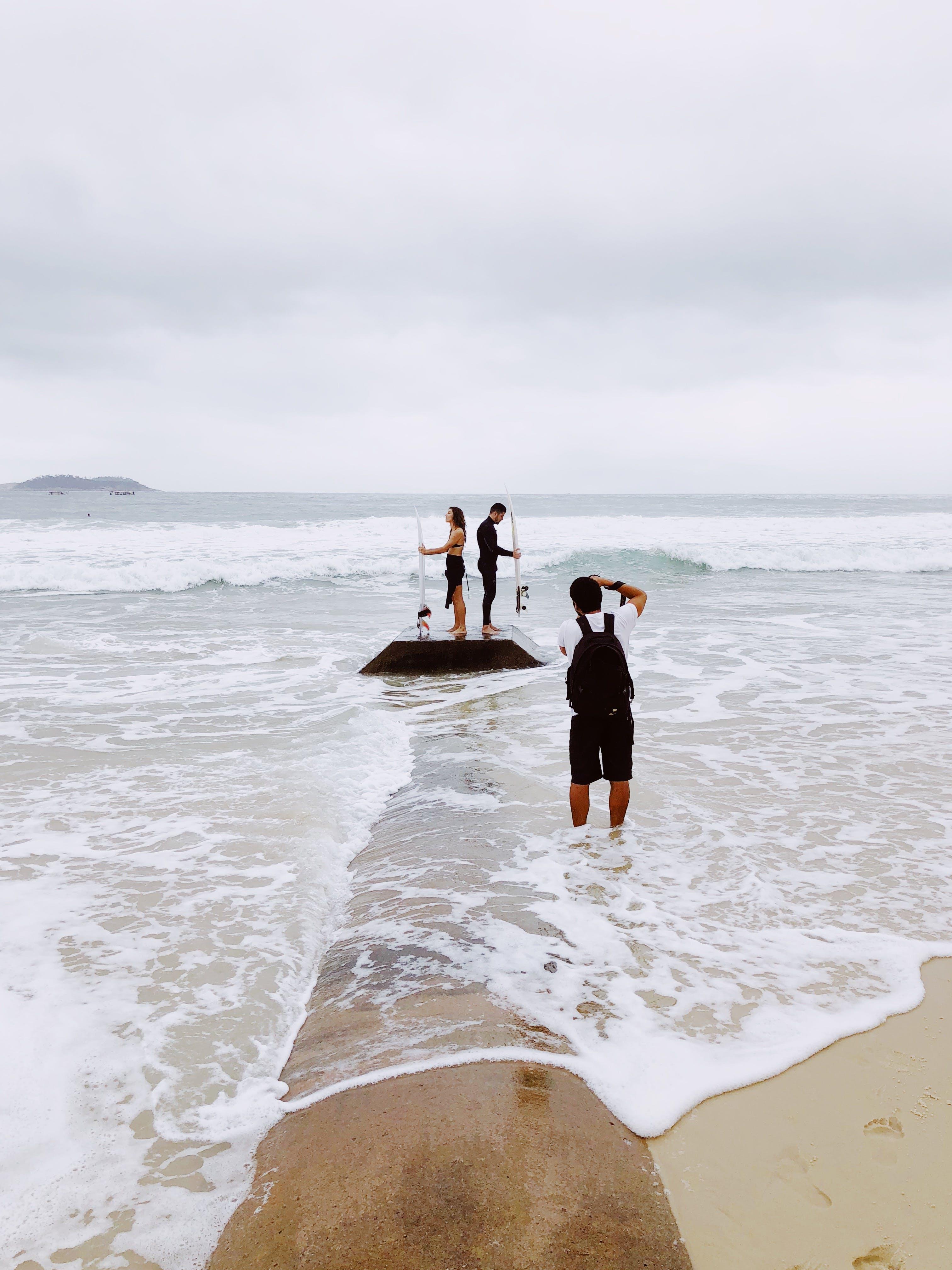 Three Person on Seashore