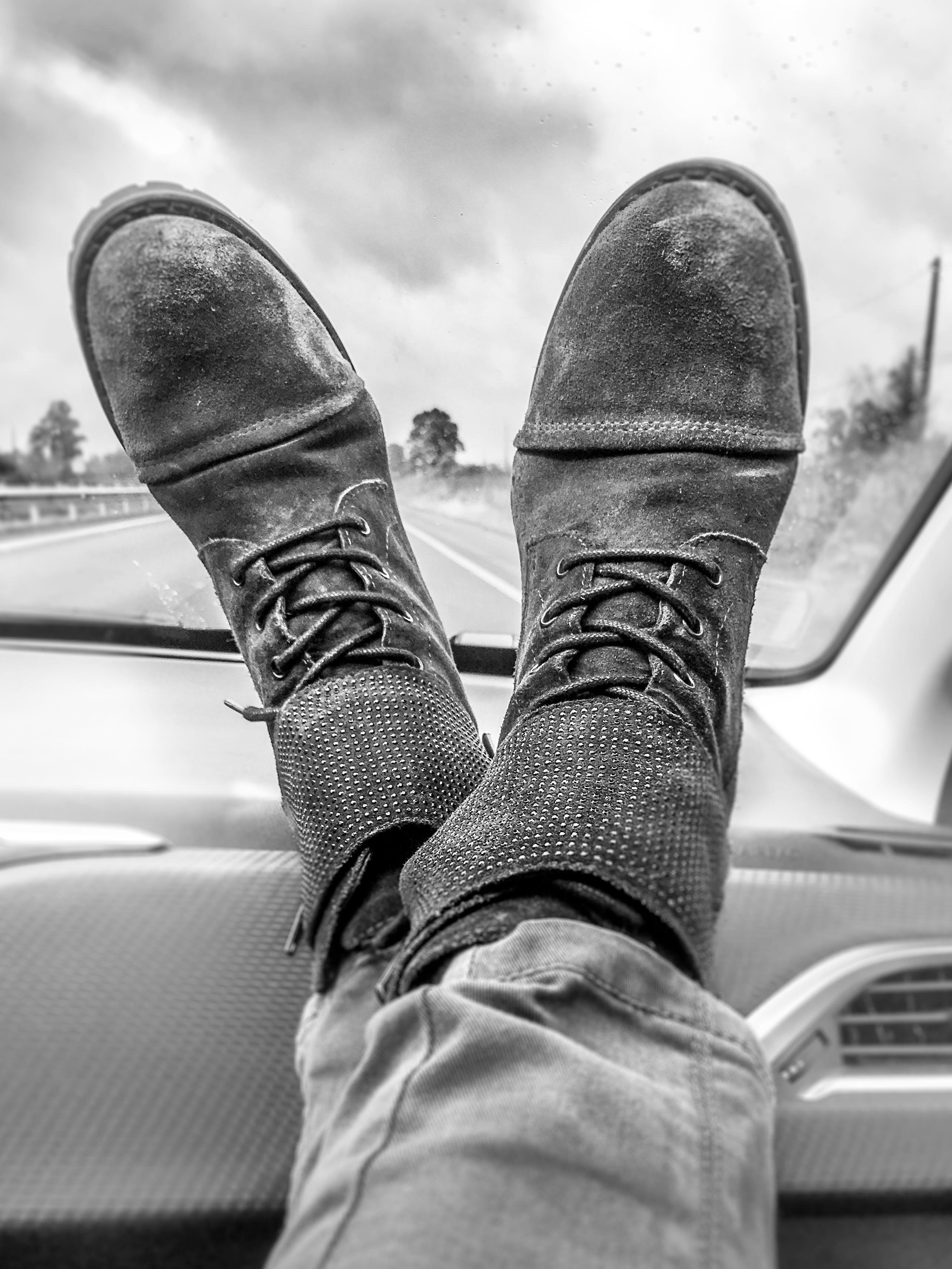 Grayscale Photography of Person's Feet on Vehicle Dashboard