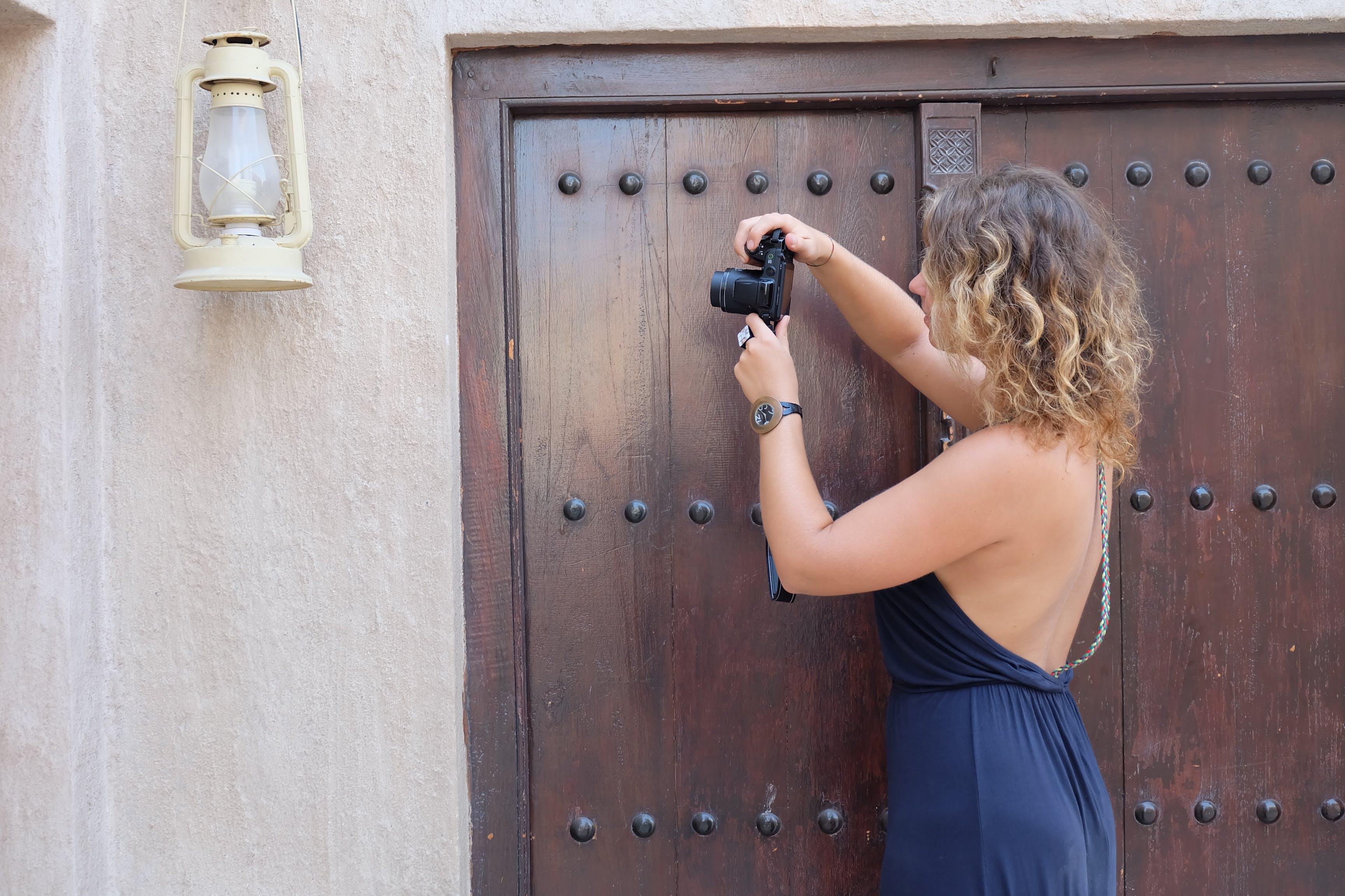 Woman Taking a Photo of Kerosene Lantern Hanged on Wall