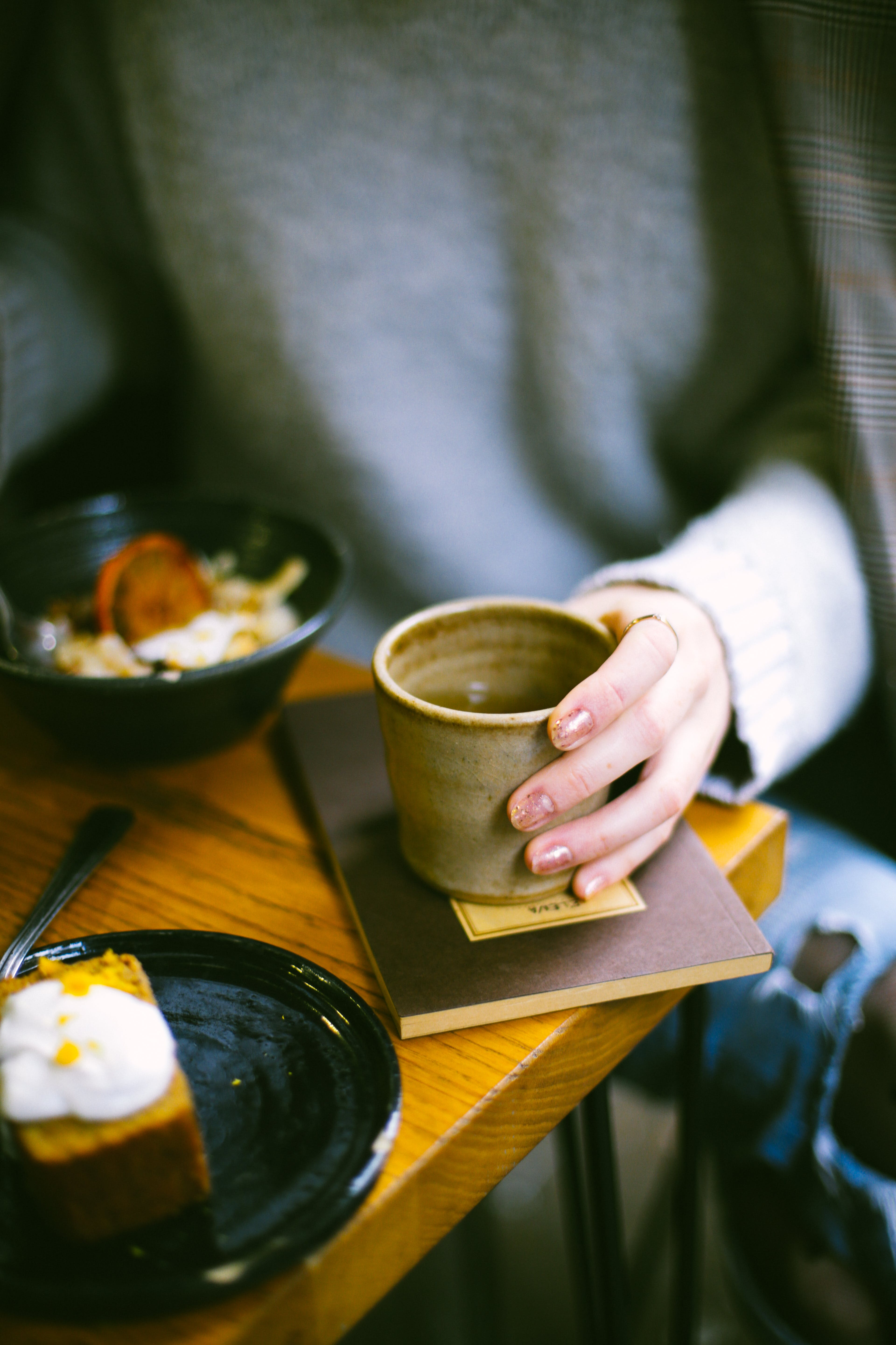Person Holding Mug on Top of Brown Book