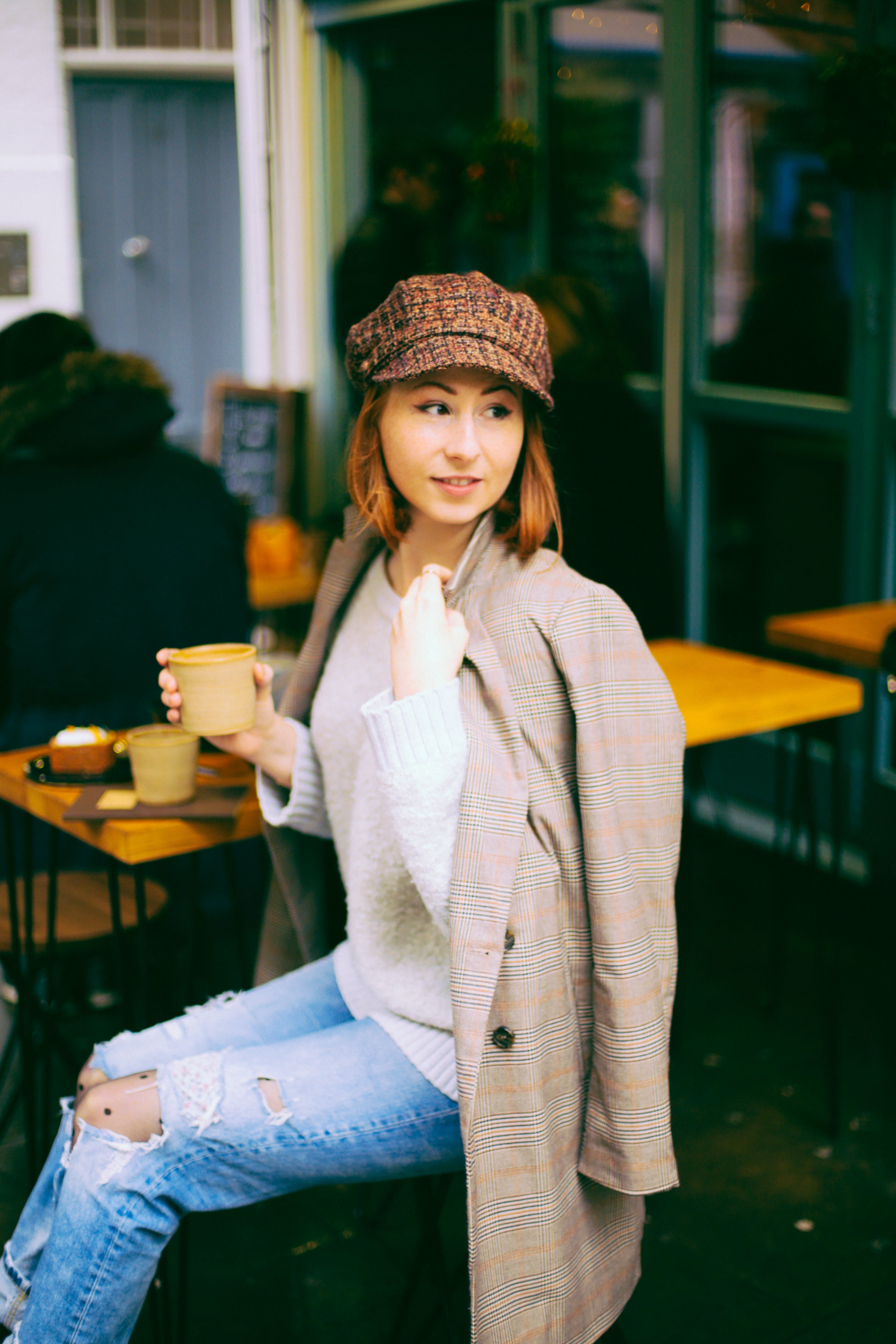 Woman Wearing Brown Coat Holding Cup Sitting on Chair