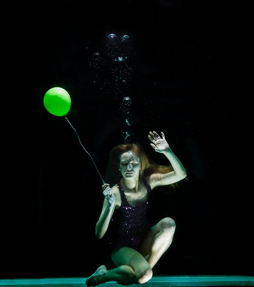 Underwater Photography of Woman Holding Green Balloon