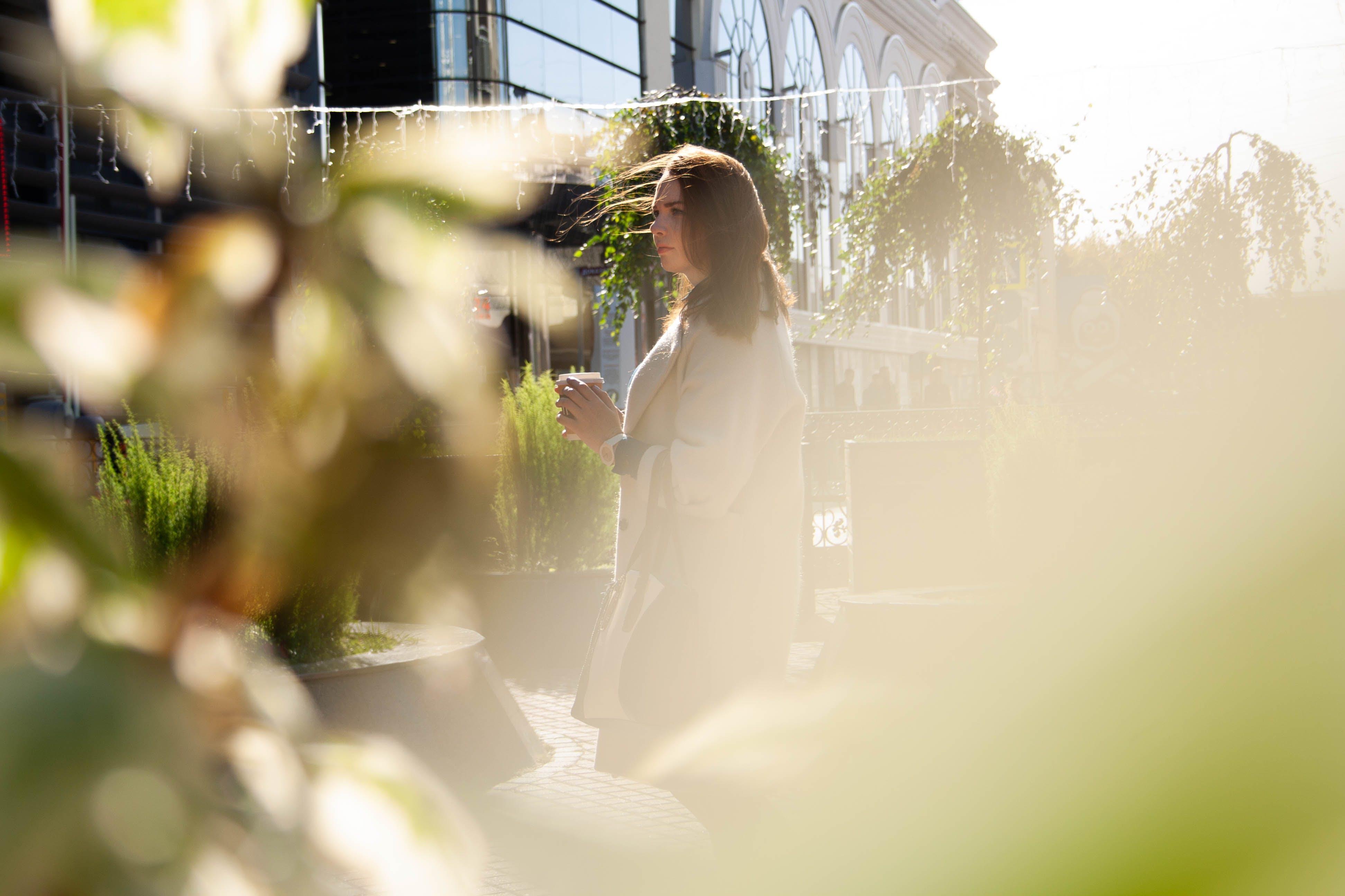 Woman in Gray Coat Standing Near Green Plants