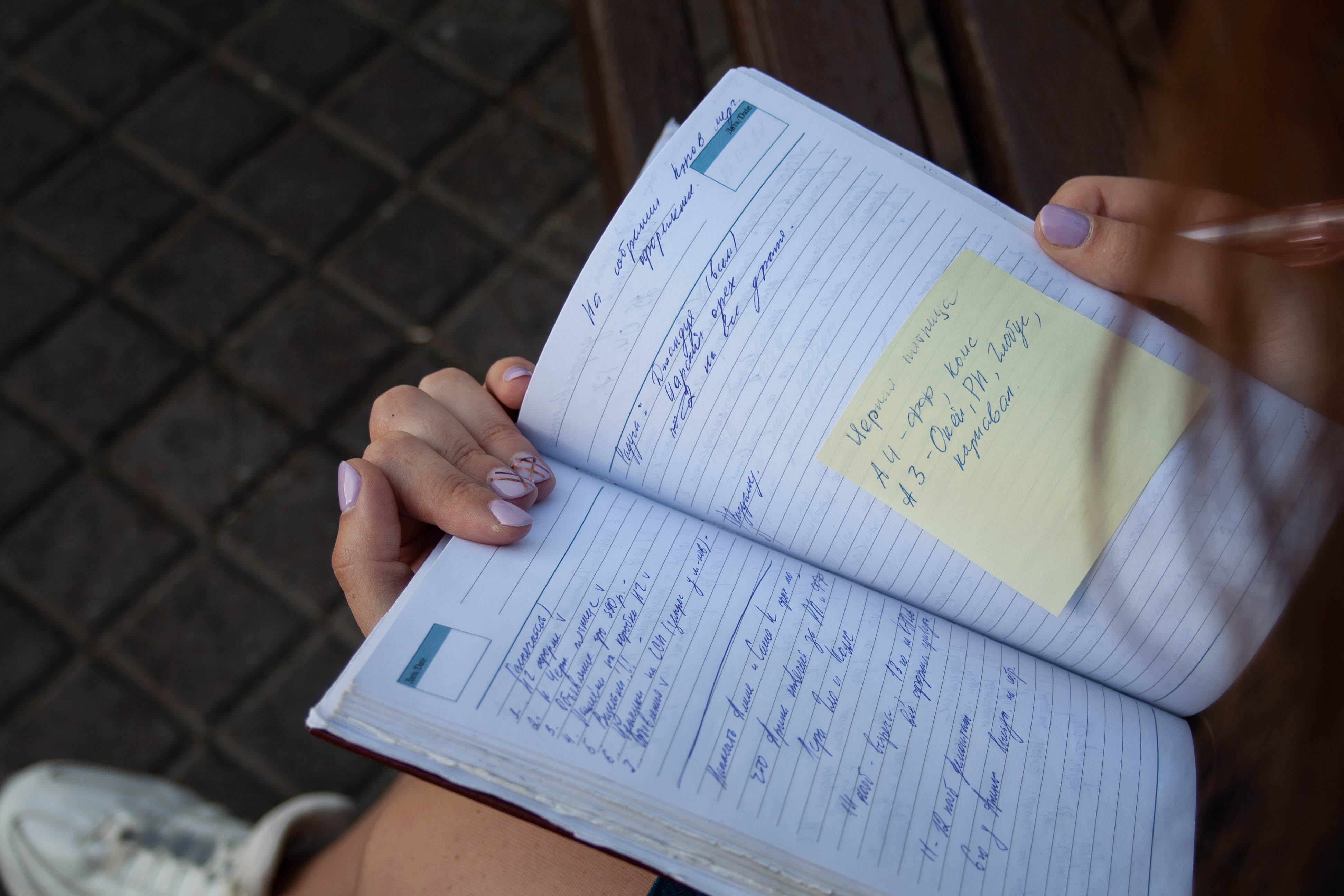 Person Holding Ruled Ntoebook With Yellow Sticky Note