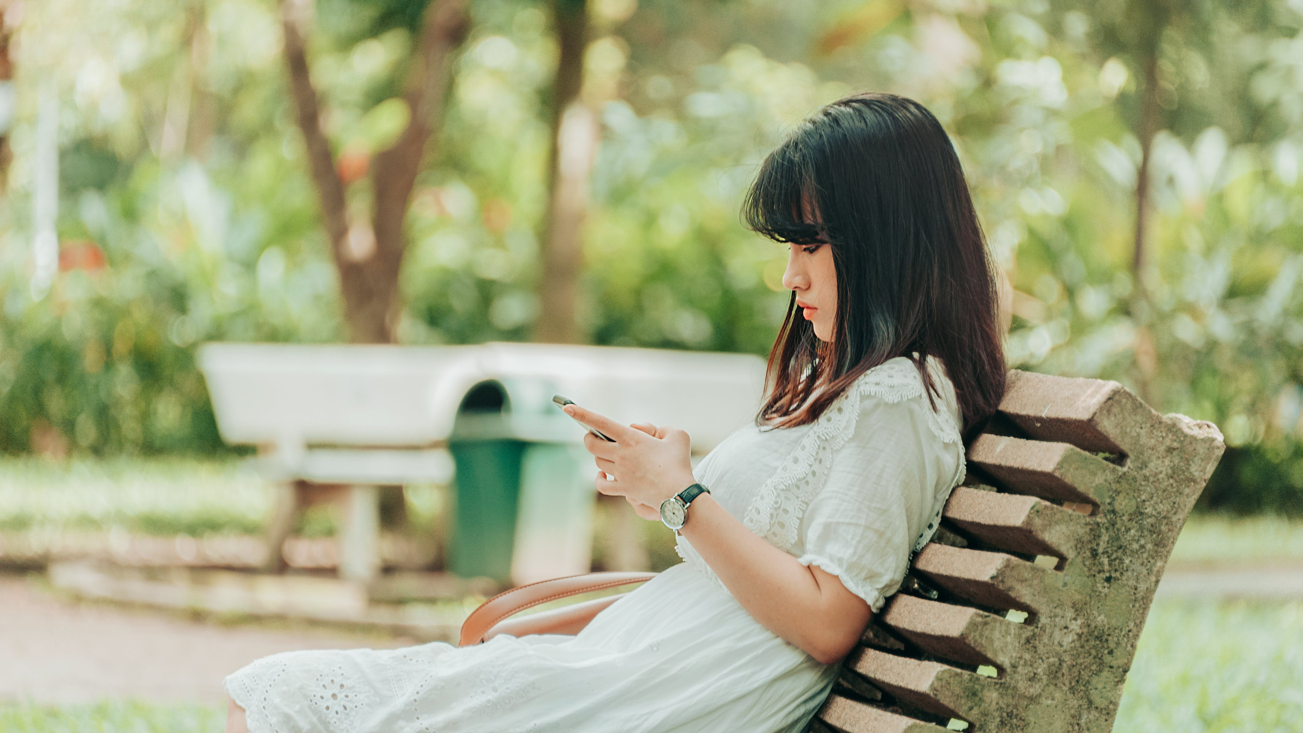 Woman Sitting on Bench Using Smartphone