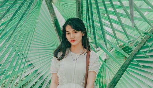 Woman Standing Beside Green Plant