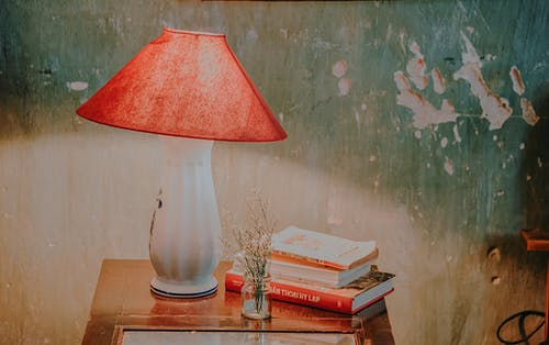 White and Red Table Lamp, Assorted-color Books, and White Petaled Flower in Clear Glass Vase on Brown Wooden End Table
